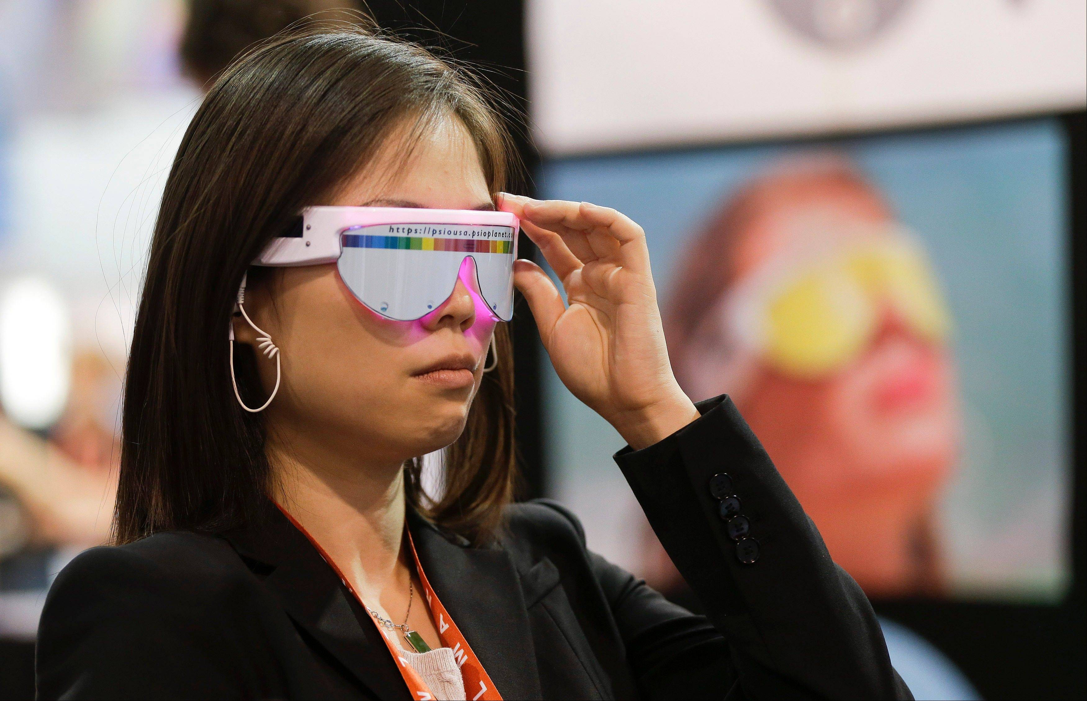 An industry affiliate tries a pair of PSiO Mind Booster stress management glasses at the Consumer Electronics Show, Wednesday, Jan. 9, 2013, in Las Vegas. The glasses use precise light and sound rhythms to stimulate the brain and influence the user's state of mind.