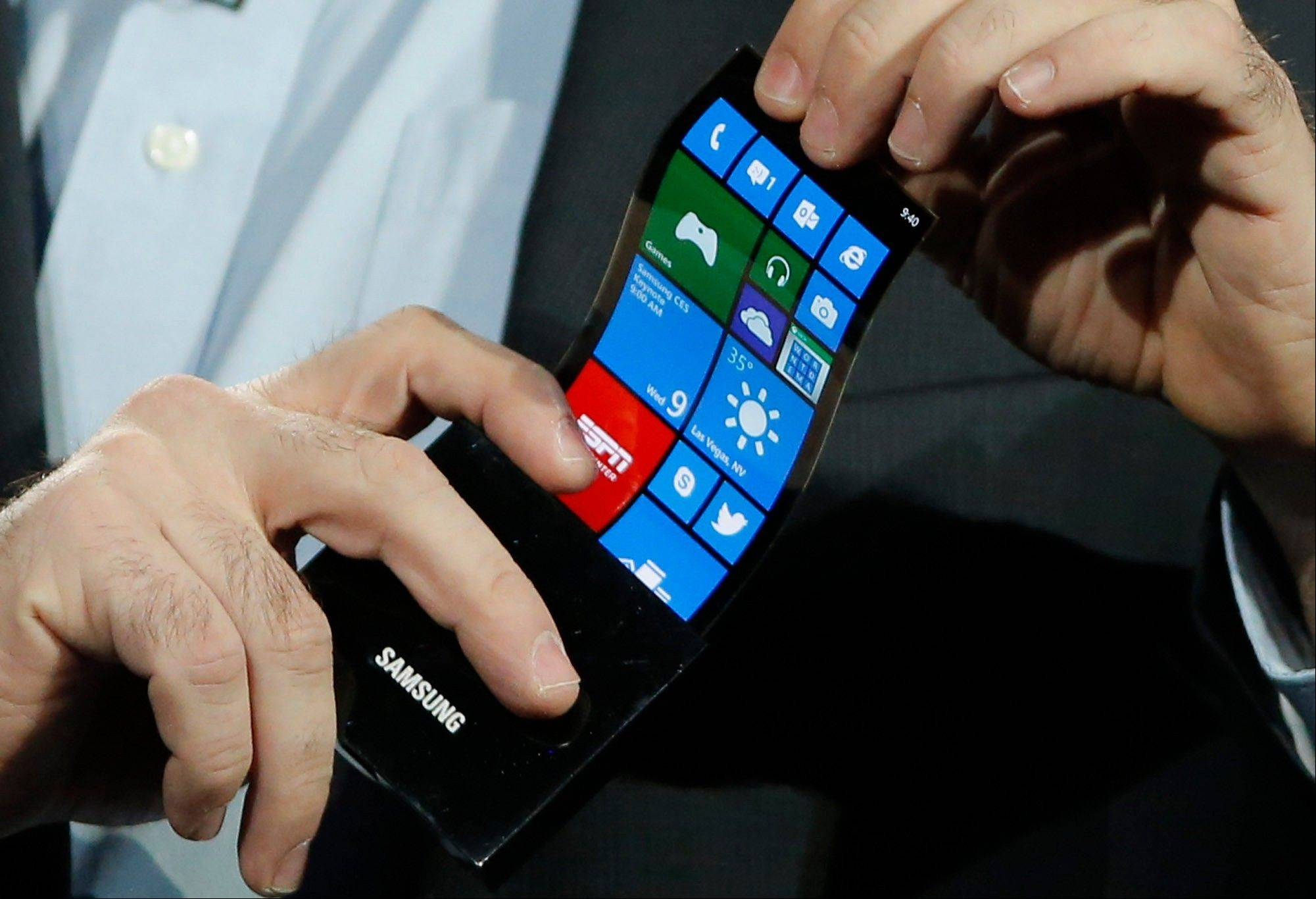 Eric Rudder, chief technical strategy officer of Microsoft, holds a prototype Windows smartphone with a flexible OLED display during Samsung's keynote address at the International Consumer Electronics Show in Las Vegas, Wednesday, Jan. 9, 2013.