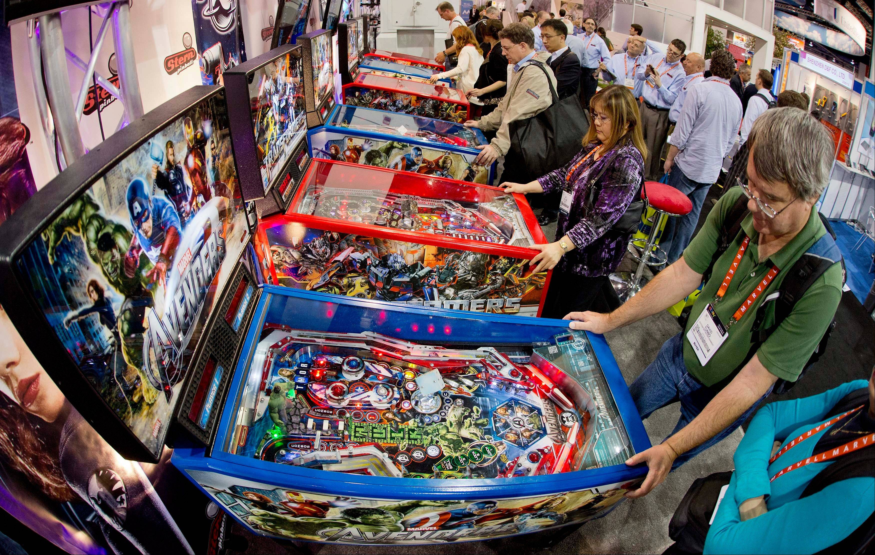 Convention goers play on a bank of pinball machines at the Consumer Electronics Show, Wednesday, Jan. 9, 2013, in Las Vegas.