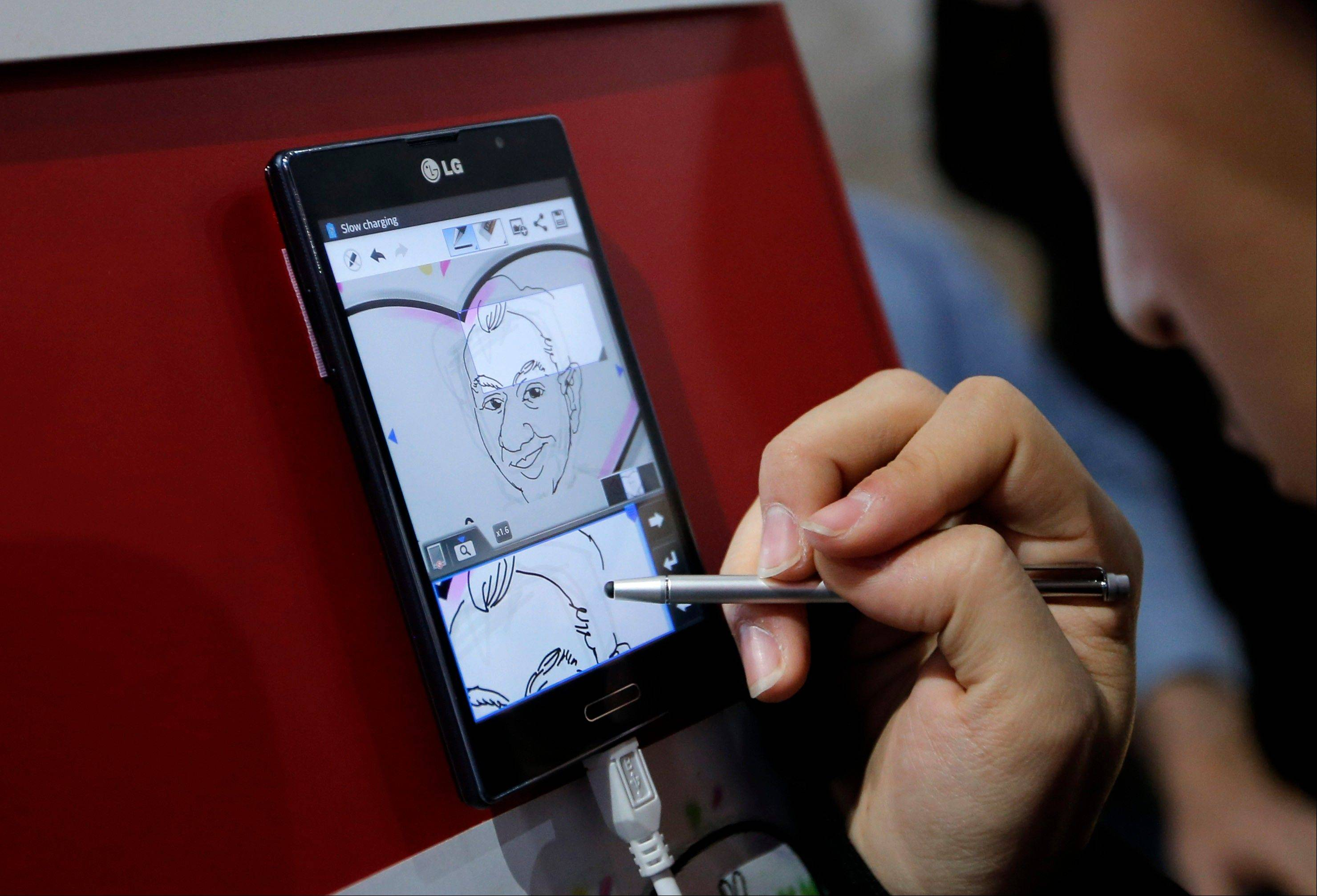 An artist draws a caricature to demonstrate the Panorama Note feature on LG smartphones at the International Consumer Electronics Show in Las Vegas, Tuesday, Jan. 8, 2013.