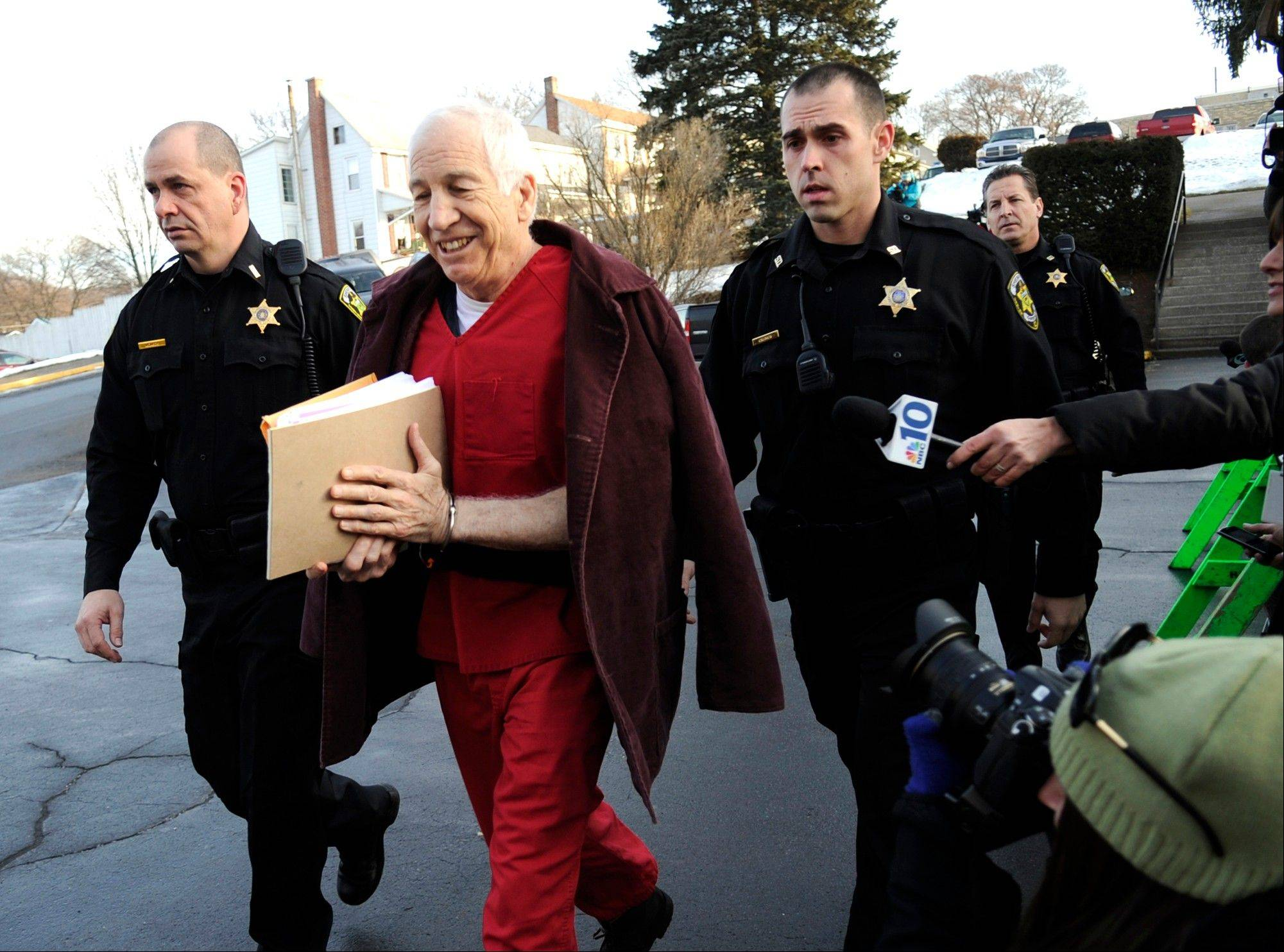 Former Penn State University assistant football coach Jerry Sandusky, center, arrives at the Centre County Courthouse for a post-sentence motion in Bellefonte, Pa., Thursday, Jan. 10, 2013. The hearing is expected to delve into the legal challenges filed by Sandusky's lawyers, including their claim that a deluge of prosecution materials swamped the defense. Sandusky is serving a 30- to 60-year prison sentence after being convicted in June of 45 counts of child sexual abuse.