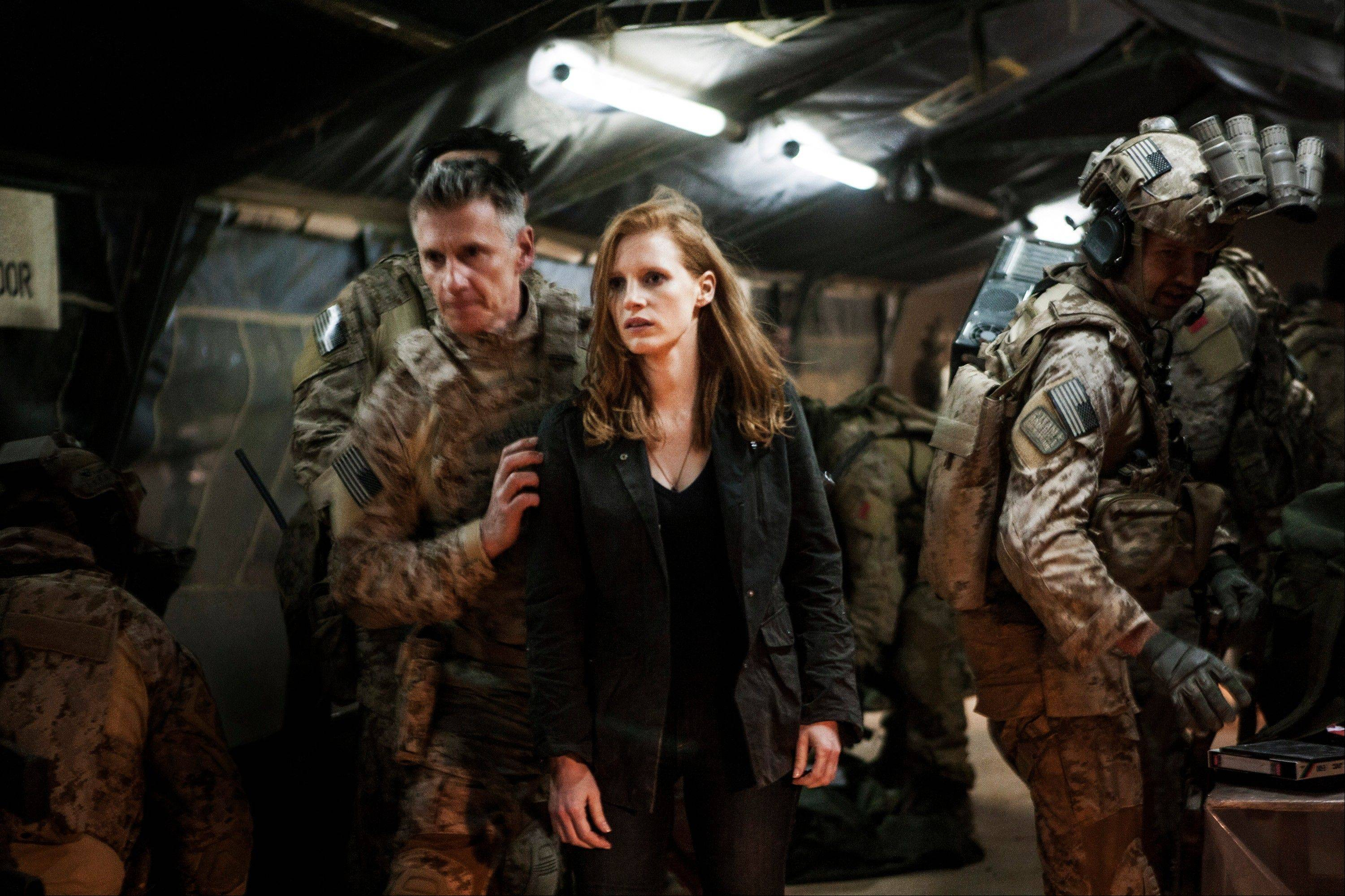 "In this undated publicity photo released by Columbia Pictures Industries, Inc., Jessica Chastain, center, plays a member of the elite team of spies and military operatives, stationed in a covert base overseas, with Christopher Stanley, left, and Alex Corbet Burcher, right, who secretly devote themselves to finding Osama Bin Laden in Columbia Pictures' new thriller, ""Zero Dark Thirty."