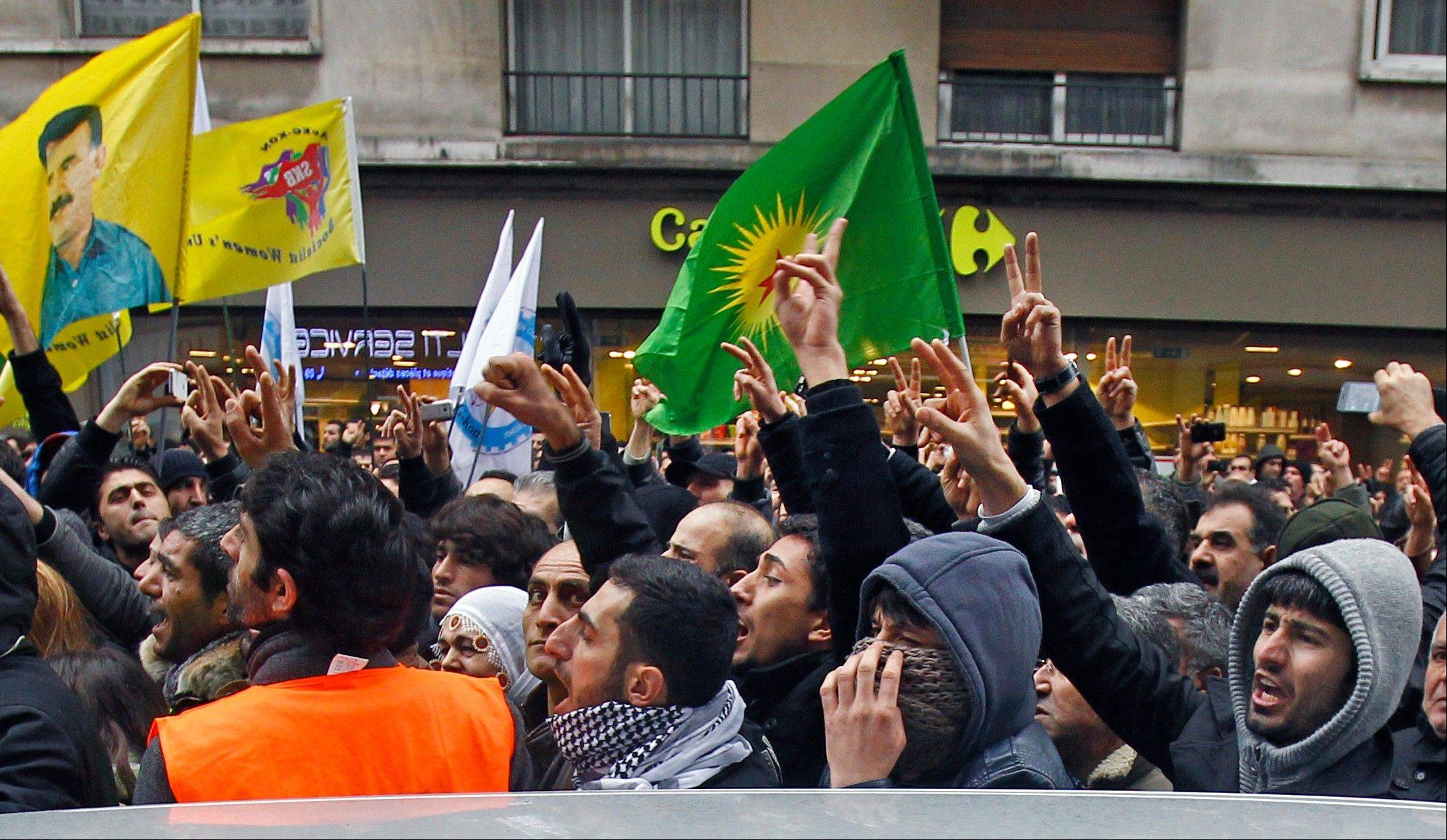 Kurdish people react as three bodies of the killed Kurdish women are taken out of the building in Paris, Thursday Jan. 10, 2012. Police say three Kurdish women have been shot dead at a pro-Kurdish center in Paris in what the French interior minister is calling an execution.
