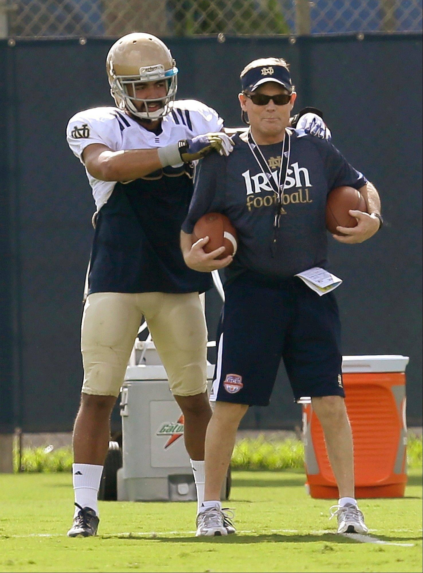 Notre Dame safety Matthias Farley, left, stands behind safeties coach Bob Elliott during practice, Thursday, Jan. 3, 2013, at the Miami Dolphins' training facility in Davie, Fla. Notre Dame is scheduled to play Alabama on Monday, Jan. 7, in the BCS national championship NCAA college football game. Farley was a soccer player before transitioning to football, first as a wide receiver and now a starting safety for No. 1 Notre Dame.