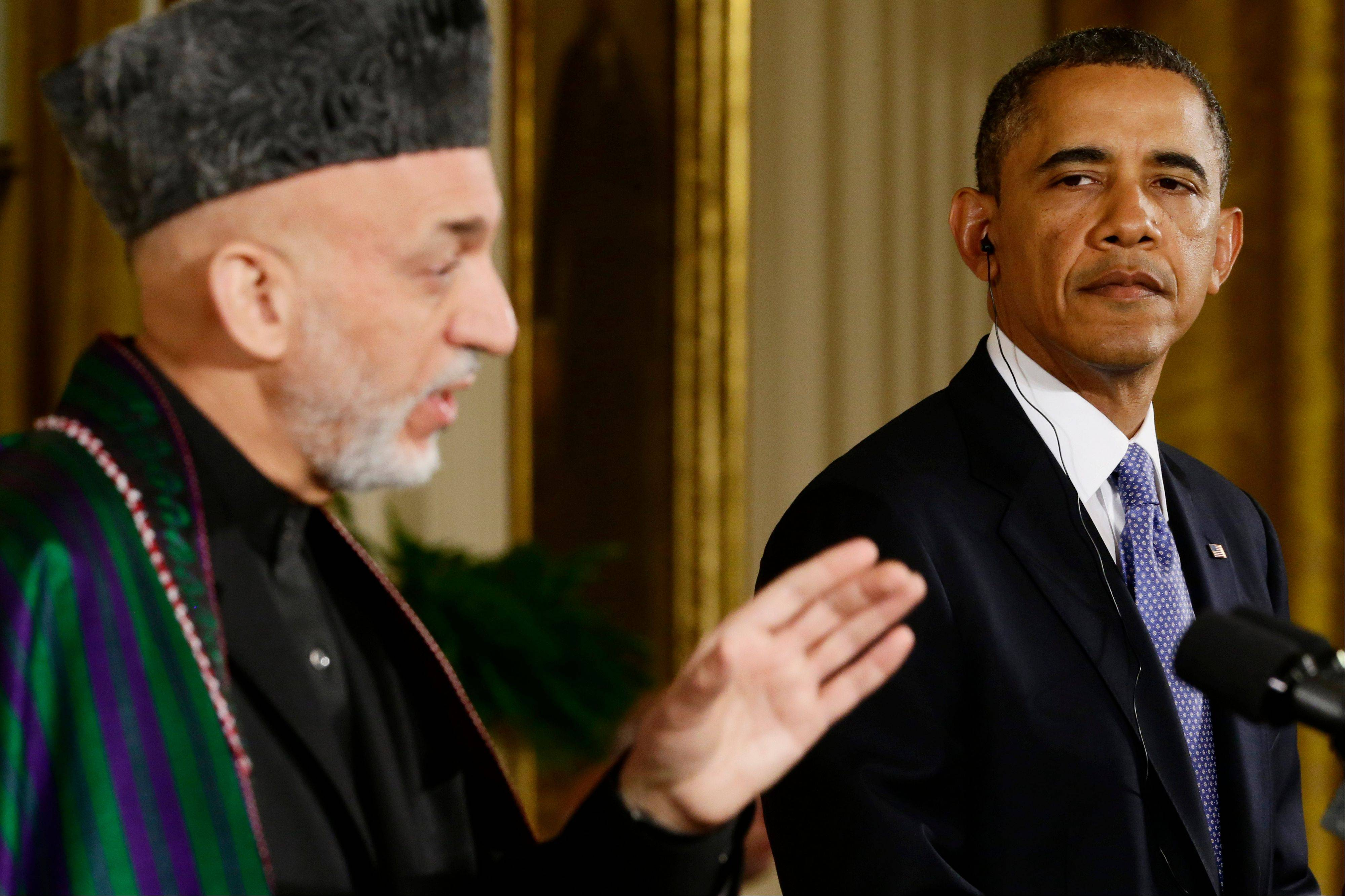 President Barack Obama listens Friday as Afghan President Hamid Karzai speaks during their joint news conference in the East Room at the White House.