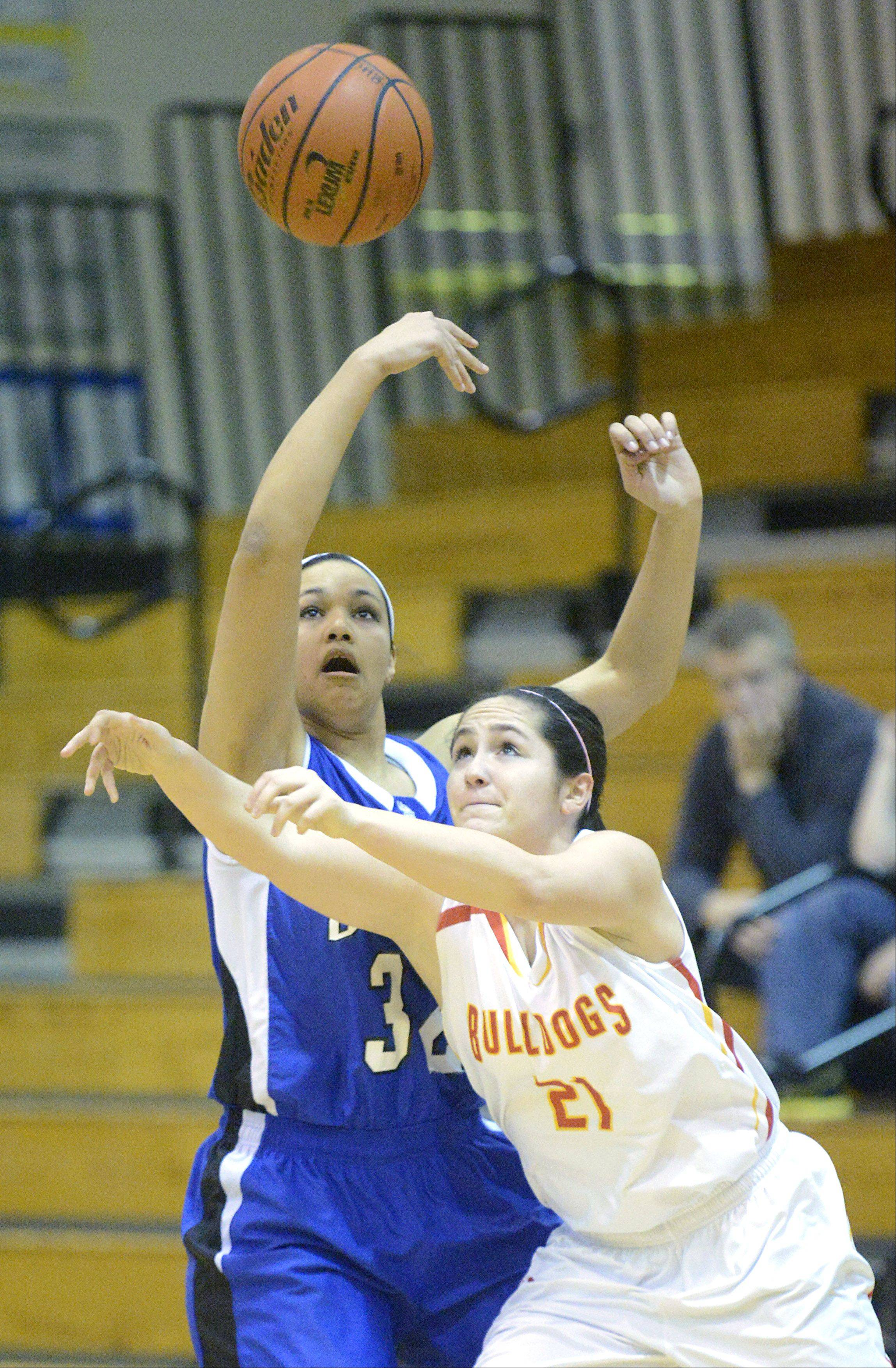 Geneva�s Sidney Santos knocks the ball upward and out of the grasp of Batavia�s Sami Villarreal in the first quarter on Friday, January 11.