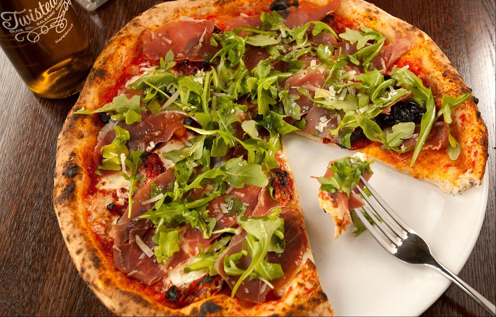 Fiamme in downtown Naperville creates oven-fired pizzas, like this one topped with fresh mozzarella, cherry tomato, prosciutto and arugula.
