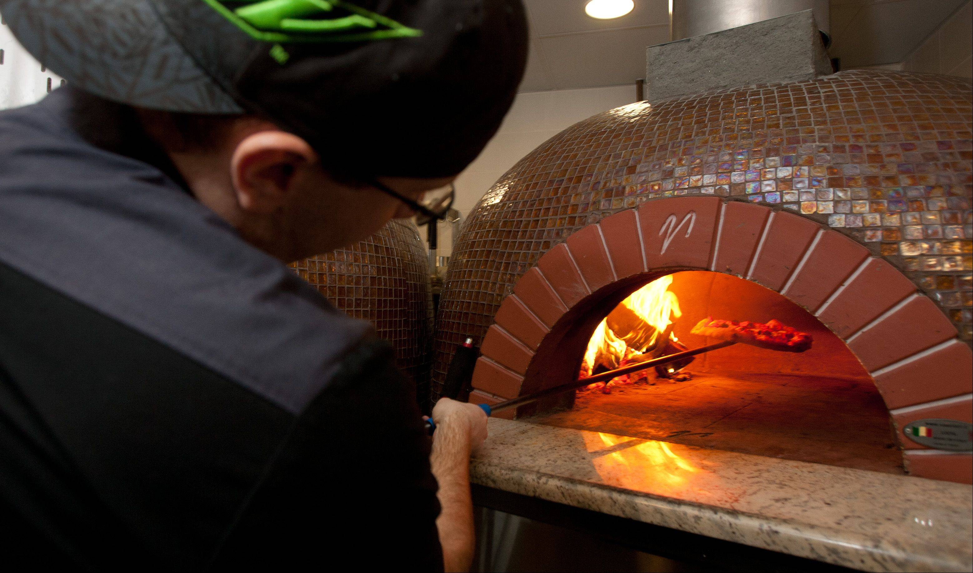 Ryan Craig, Fiamme's executive chef, makes a Regina Margherita pizza.