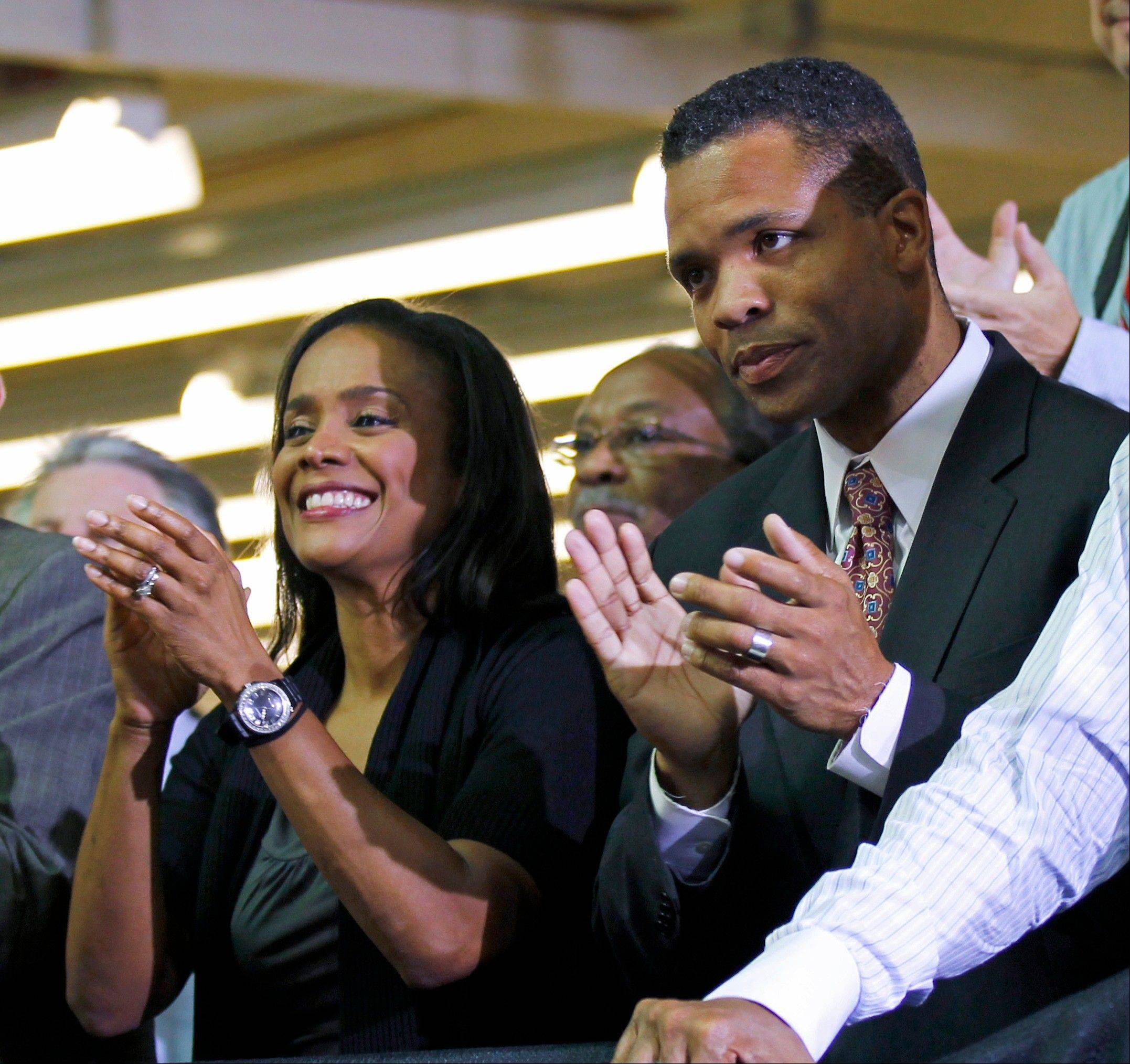 Then-Rep. Jesse Jackson Jr. right, and his wife, Sandi Jackson, applaud as President Barack Obama is introduced at the Ford assembly plant in Chicago. Sandi Jackson has resigned from the Chicago City Council. Her husband resigned from Congress in November.