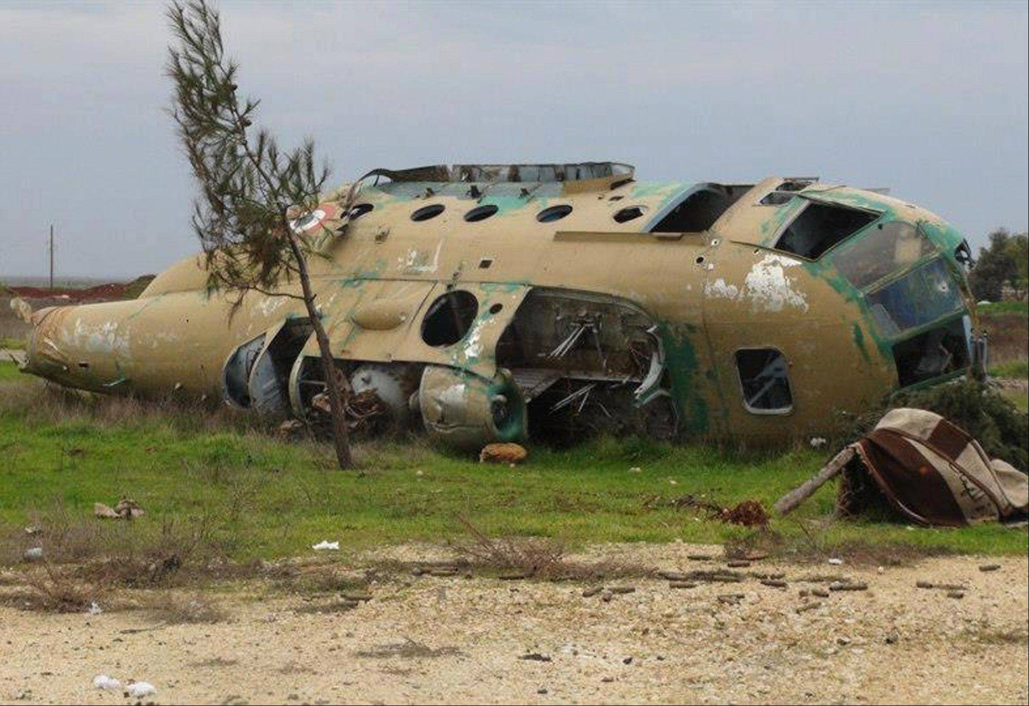 This citizen journalism image provided by Edlib News Network, ENN, which has been authenticated based on its contents, shows a damaged Syrian air force helicopter at Taftanaz air base that was captured by the rebels on Friday.