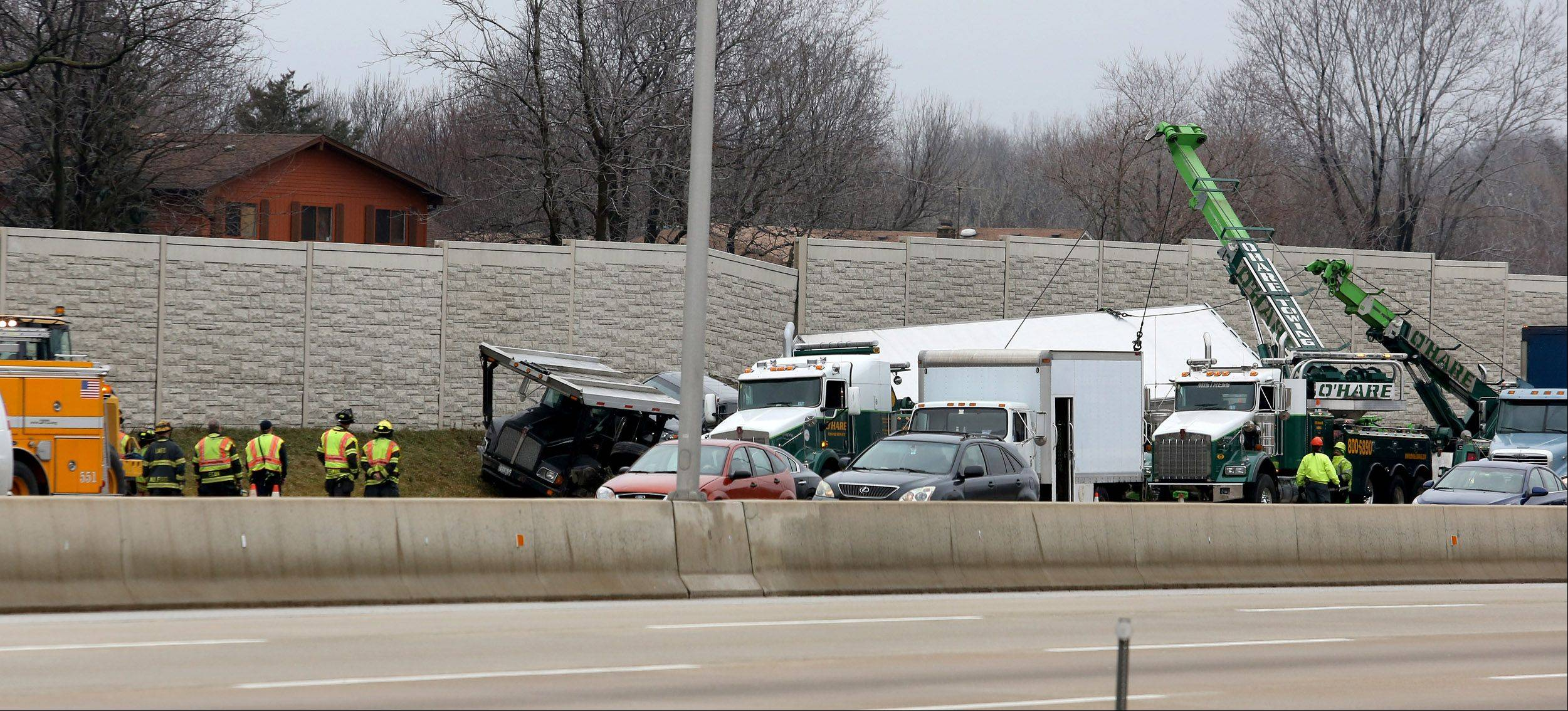 Crews work to clear away three damaged vehicles Friday along I-88 between Naperville Road and Yackley Avenue.