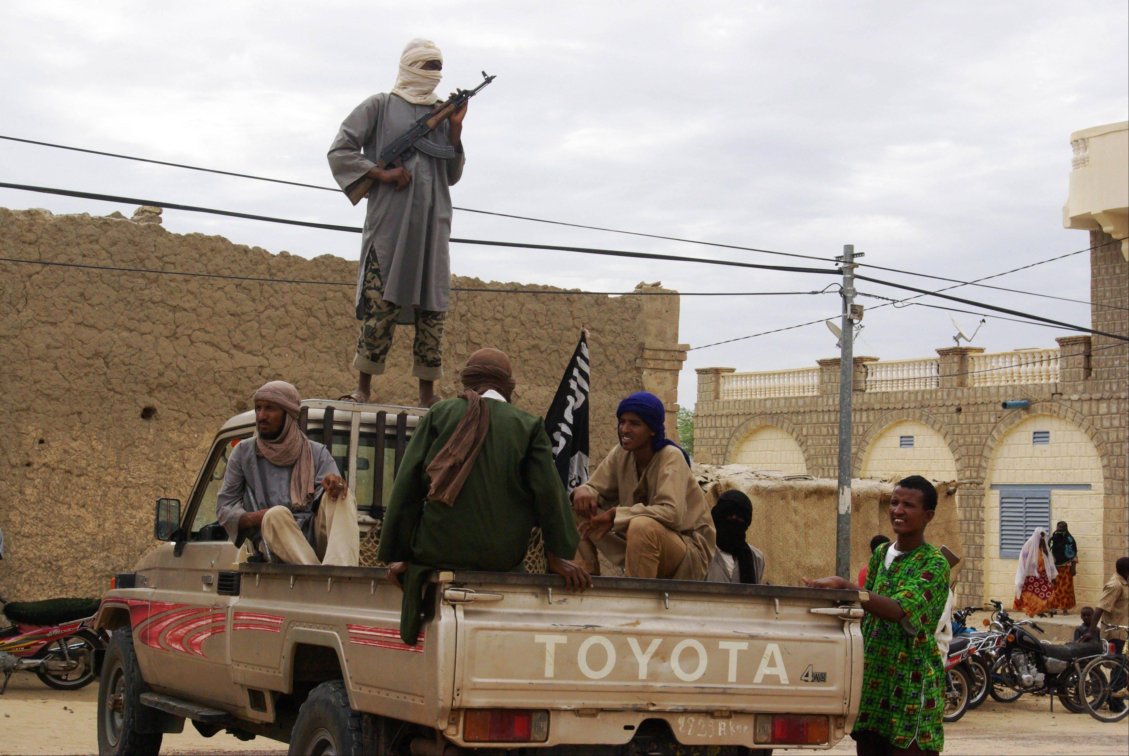 Fighters from Islamist group Ansar Dine stand guard in Timbuktu, Mali, as they prepare to publicly lash a member of the Islamic Police found guilty of adultery.