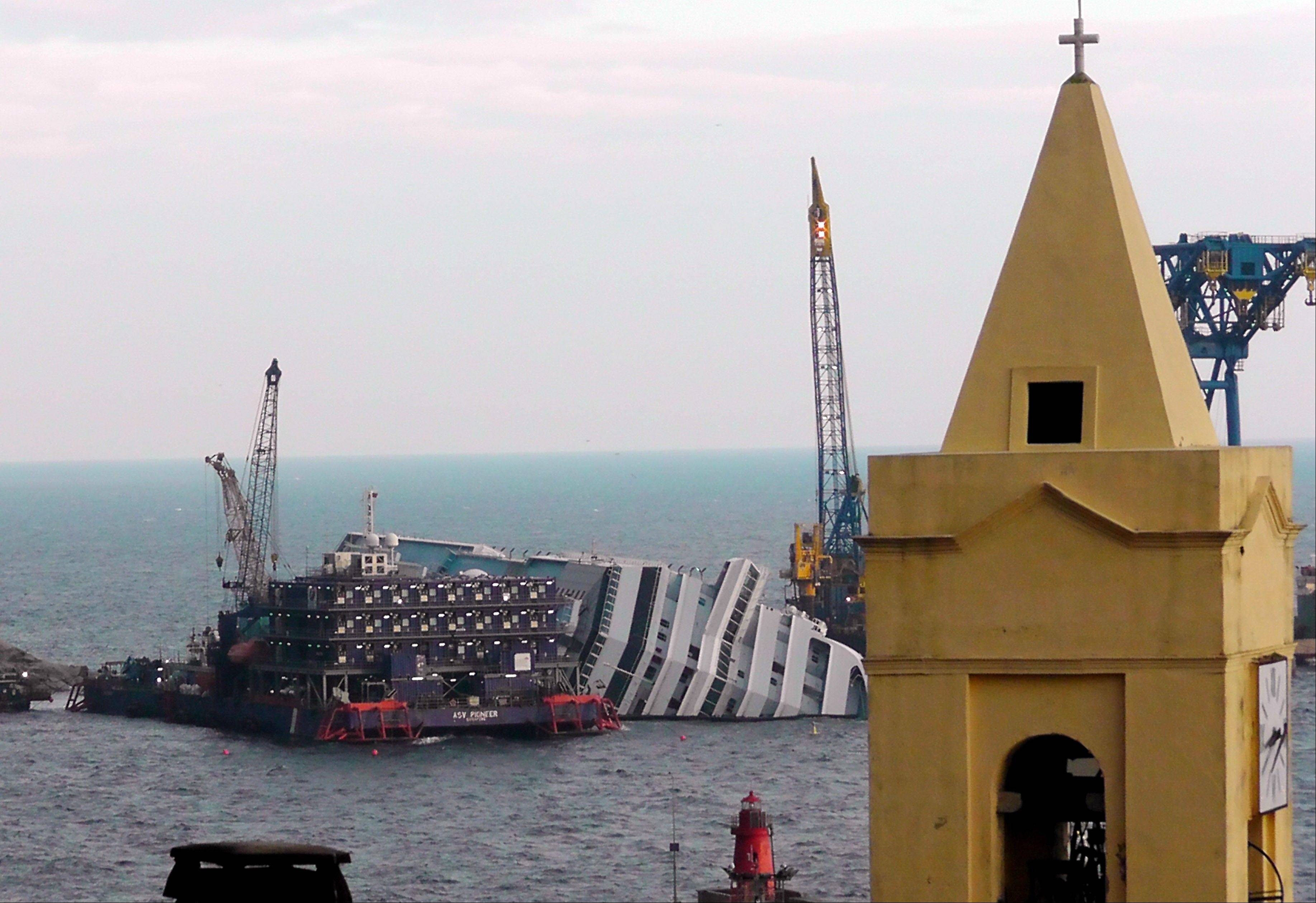 The cruise ship Costa Concordia, leaning on its side, is framed by a church bell tower in the Tuscan island of Giglio, Italy, Friday, Jan. 11, 2013. Passengers who survived the terrifying grounding and capsizing of the Costa Concordia off Tuscany have come in for a rude shock as they mark the first anniversary of the disaster on Sunday. Ship owner Costa Crociere SpA sent several passengers a letter