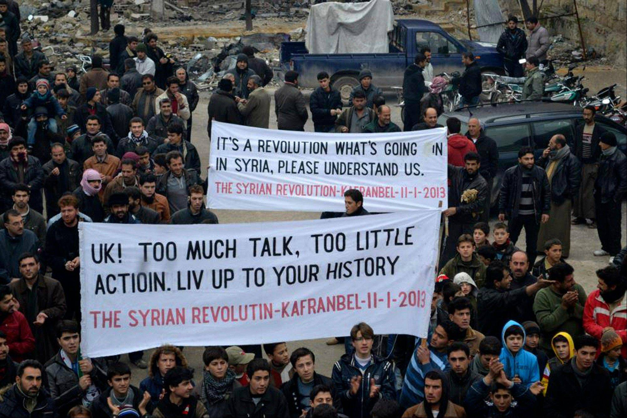 This citizen journalism image shows anti-Syrian regime protesters carrying banners during a demonstration, in Kafr Nabil town, Idlib province, northern Syria, Friday, Jan. 11, 2013. Islamic militants seeking to topple President Bashar Assad took full control of a strategic northwestern air base Friday in a significant blow to government forces, seizing helicopters, tanks and multiple rocket launchers, activists said.
