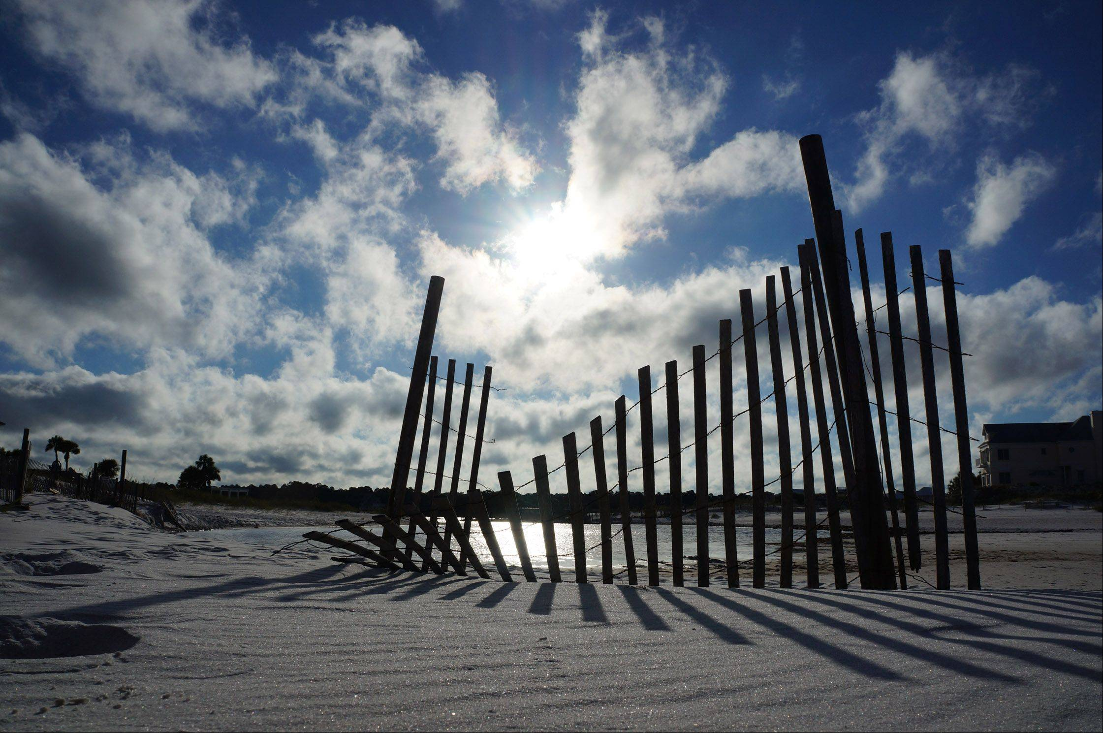A fence stands in the sand near a lake in Seaside, Florida. The lake in the background was connected to the ocean and is called a dune lake.