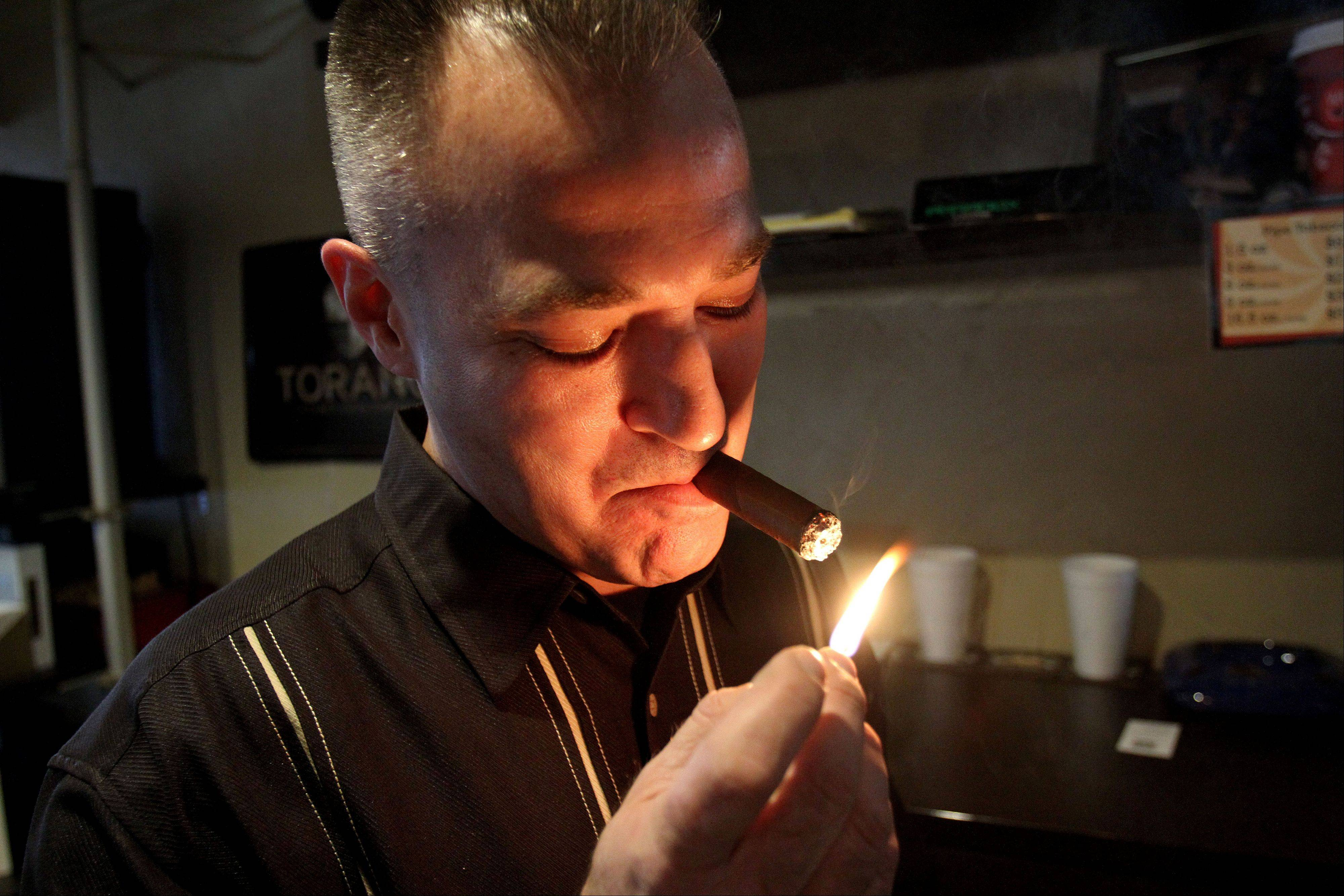 Ken Neumann, owner of Cigars and More in Libertyville lights a cigar at his shop. Neumann also is the president of the board of directors for the Lake County Haven, a women's shelter in Libertyville.