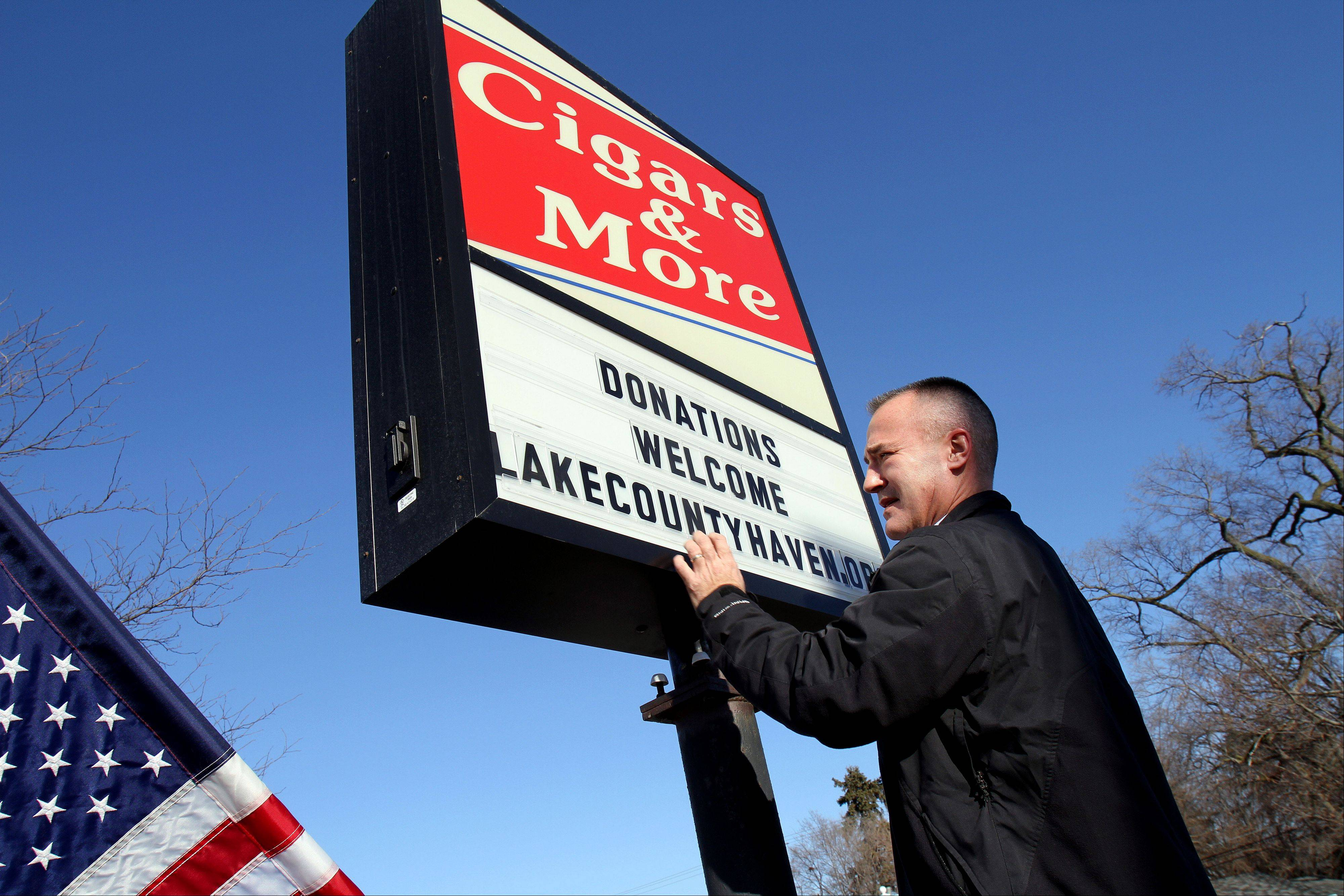 Ken Neumann posts a note welcoming donations to the Lake County Haven on the sign of his cigar shop in Libertyville.