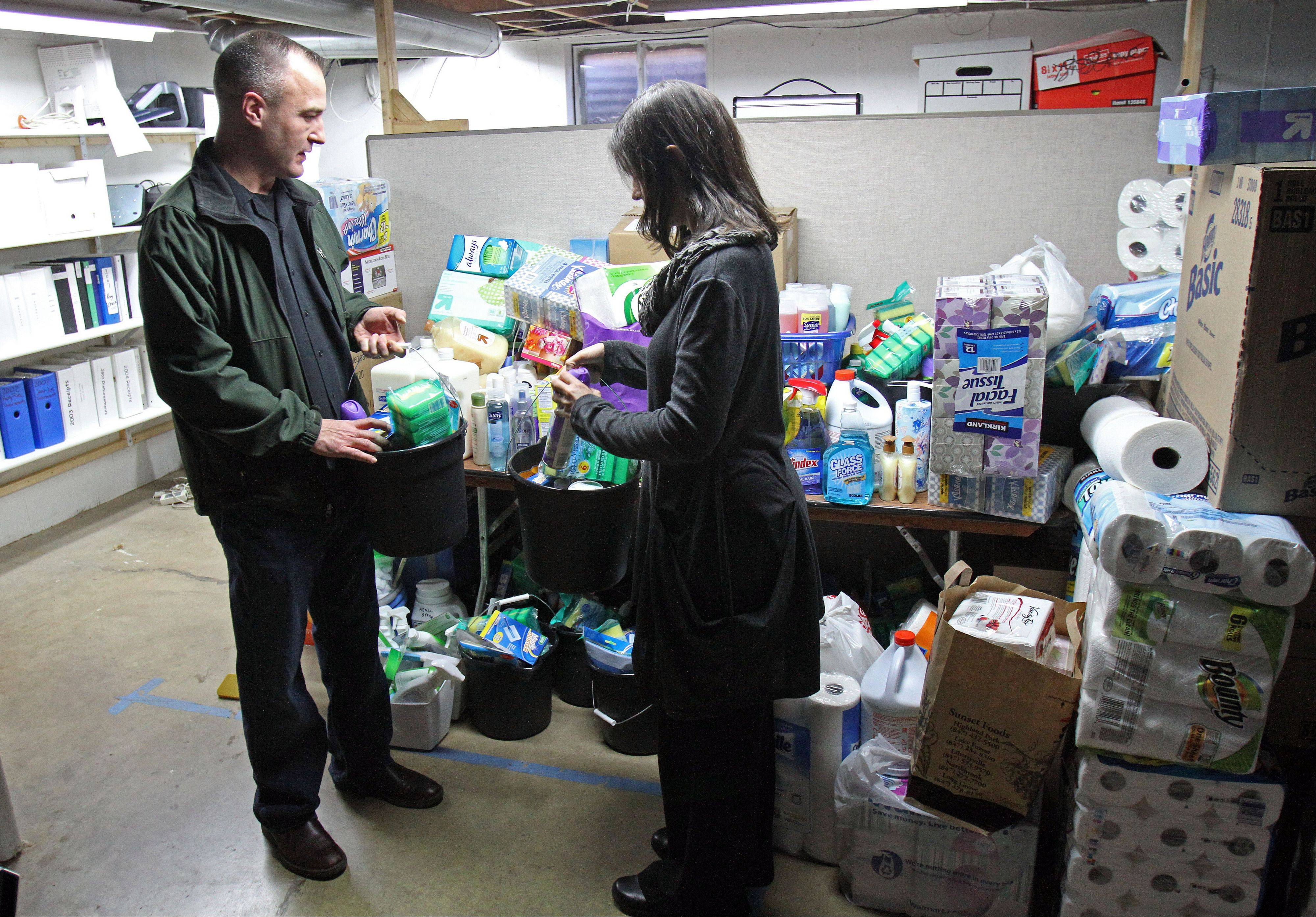 Ken Neumann, left, and Lake County Haven Executive Director Laura Sabino sort through donated items at the women's shelter in Libertyville.