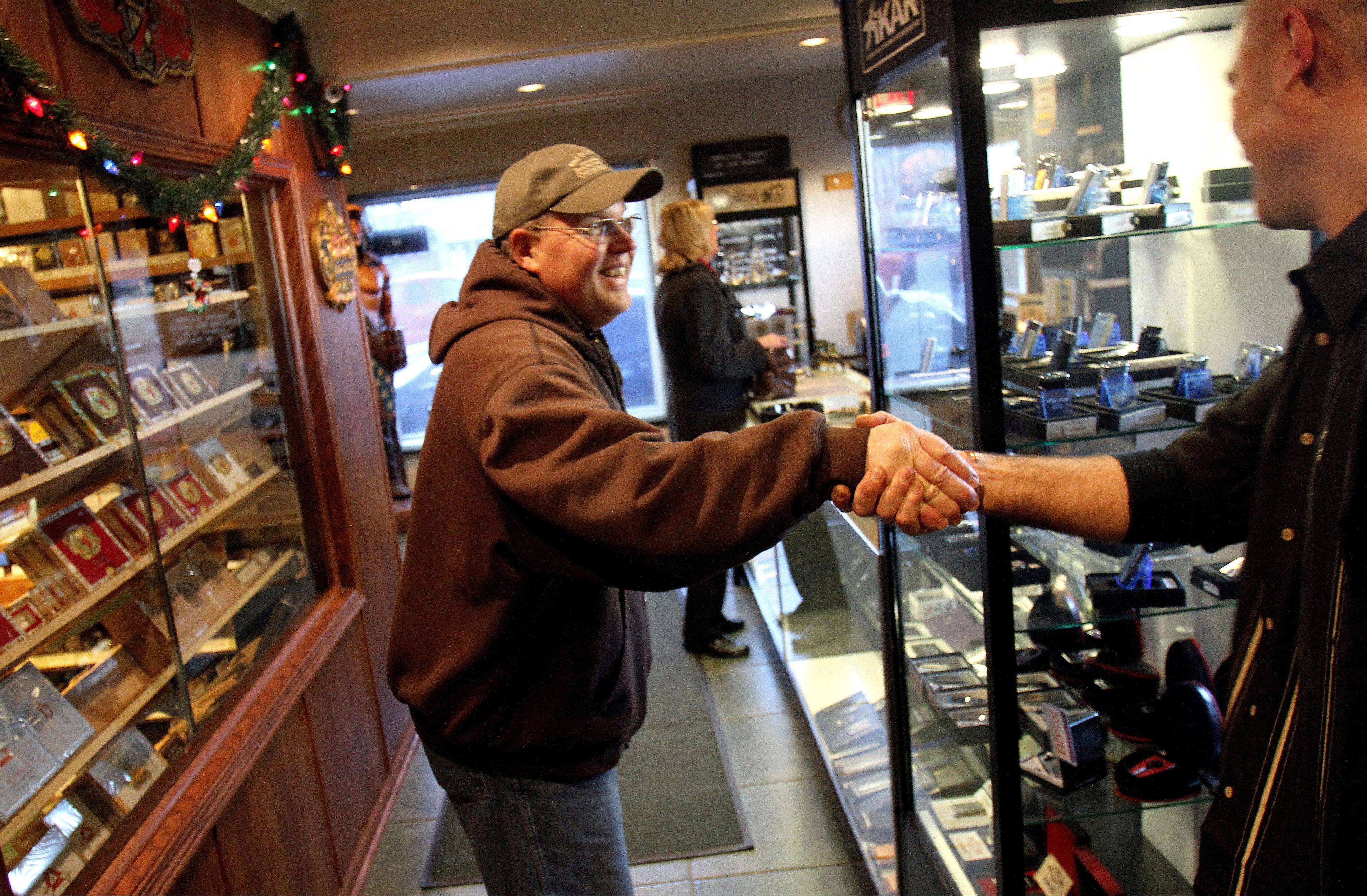 "Neumann talks with a customer at his Libertyville cigar shop. ""The Haven gave me the opportunity to become a conduit,"" said Neumann who collects many donations from his customers which go to the women's shelter."