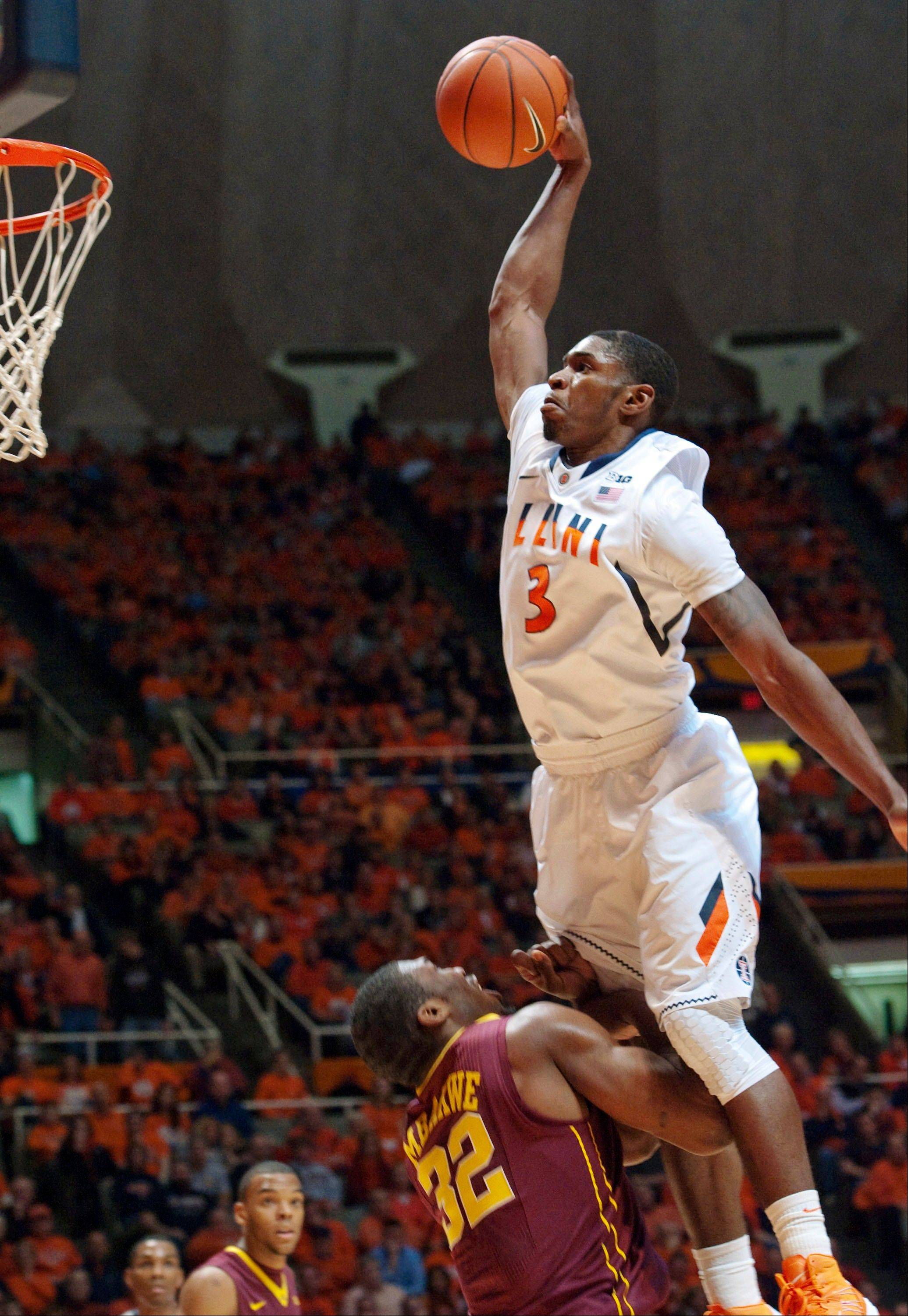 Illinois' Brandon Paul (3) elevates to the basket against Minnesota's Trevor Mbakwe (32) during the first half of their NCAA college basketball game, Wednesday, Jan. 9, 2013, in Champaign.