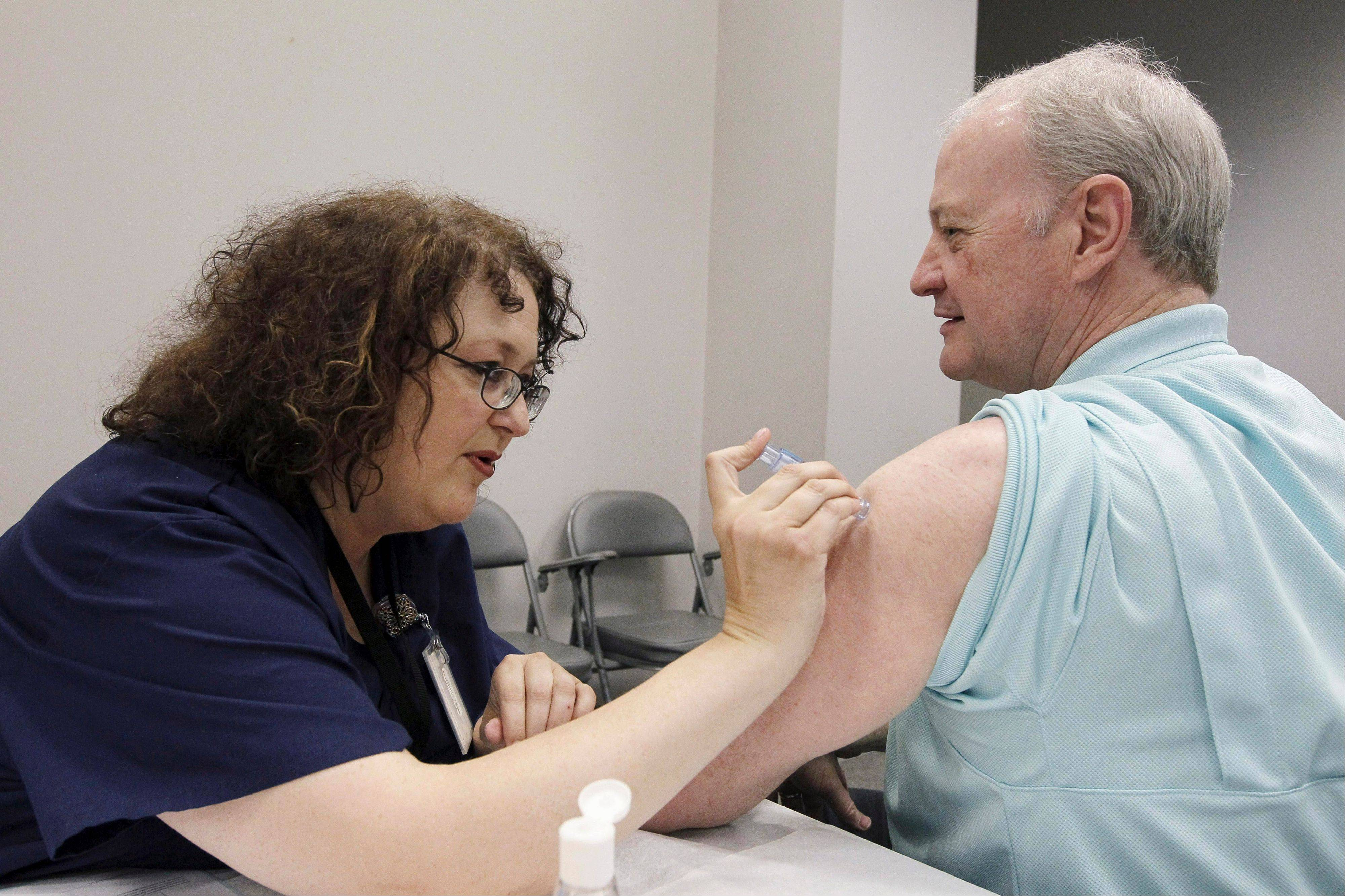 Bill Staples, a Mississippi Department of Health employee, is given a flu vaccine shot by registered nurse Rosemary Jones, also with the health department, in Jackson, Miss.