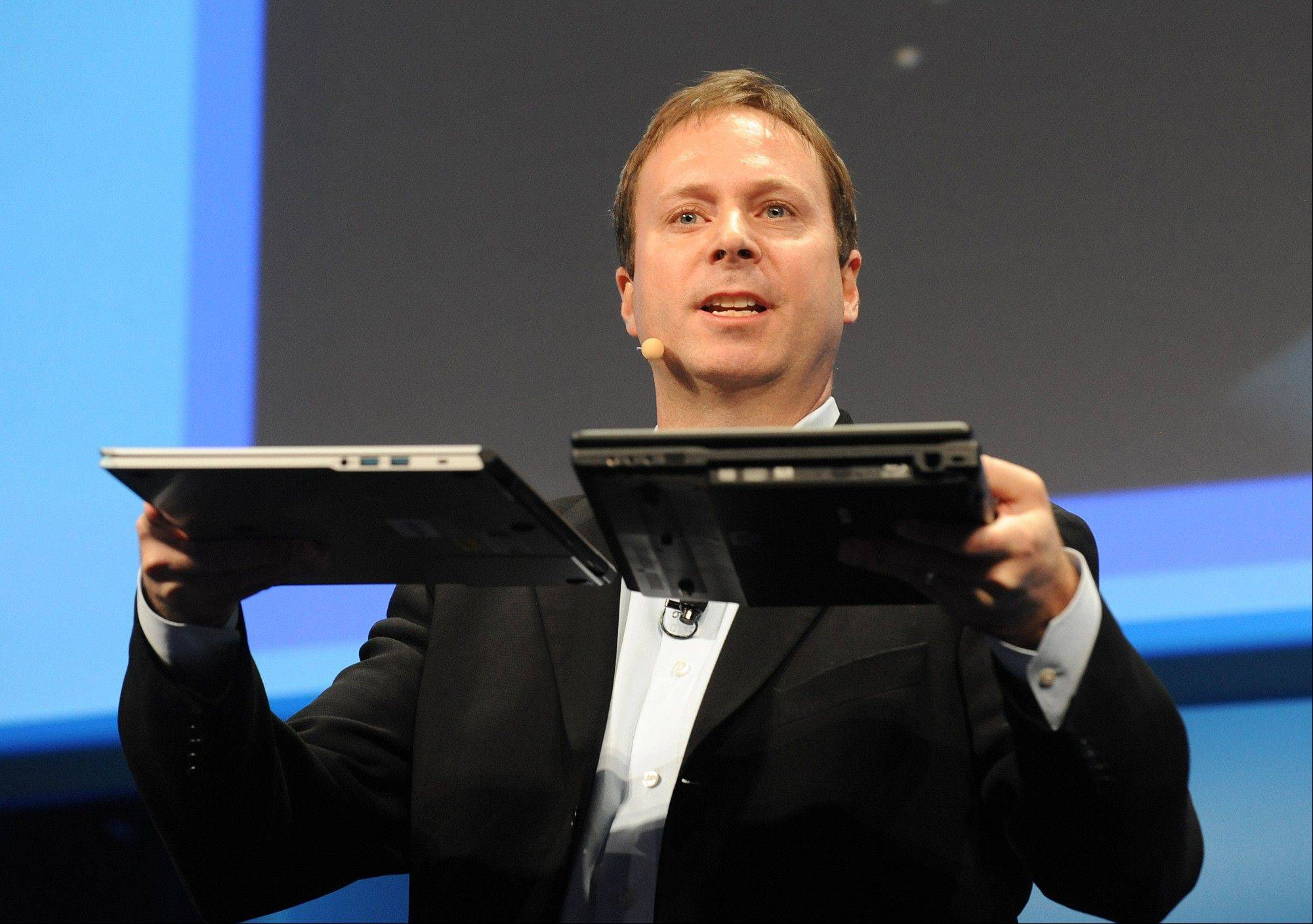 In this photo provided by Intel, Kirk Skaugen, vice president and general manager of Intelís PC Client Group shows off the new Ultrabook, left, next to an average 3-year-old laptop, at Intel's media briefing prior to opening of Consumer Electronic Show.