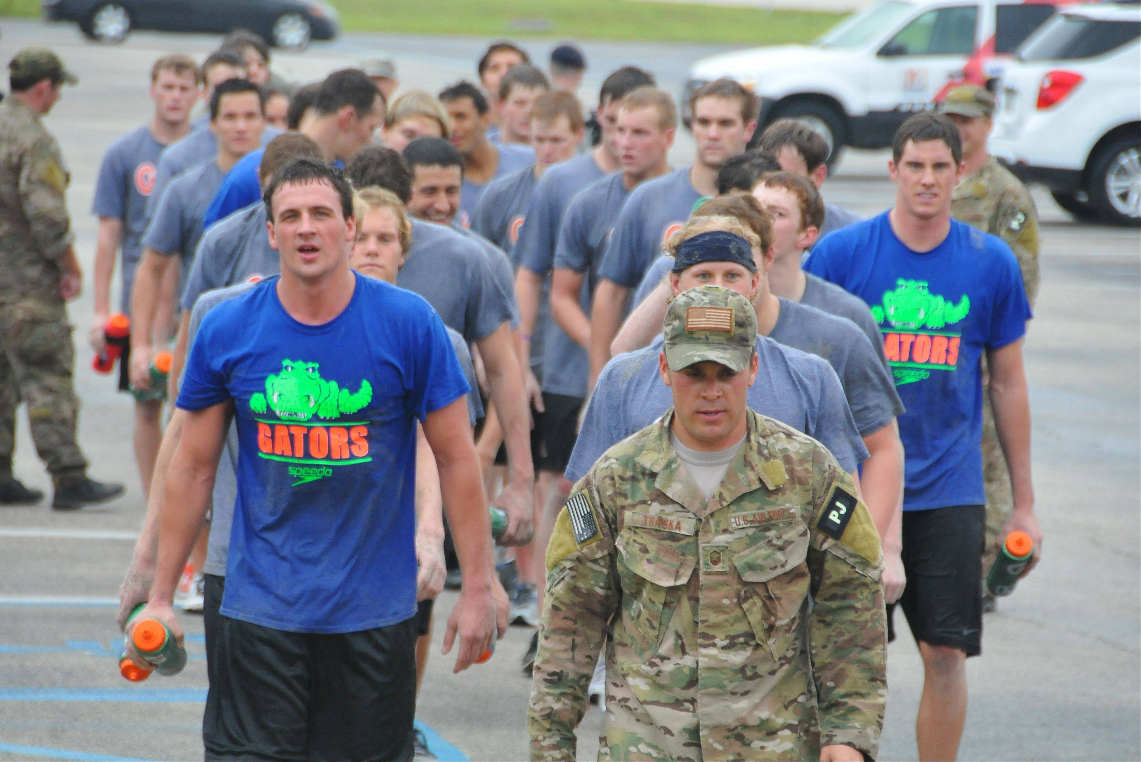 Olympic gold medalists Ryan Lochte, front left, and Conor Dwyer, wearing a Gators T-shirt at far right, and members of the University of Florida swim team workout with members of the Guardian Angels of the 920th Rescue Wing at Patrick Air Force Base.