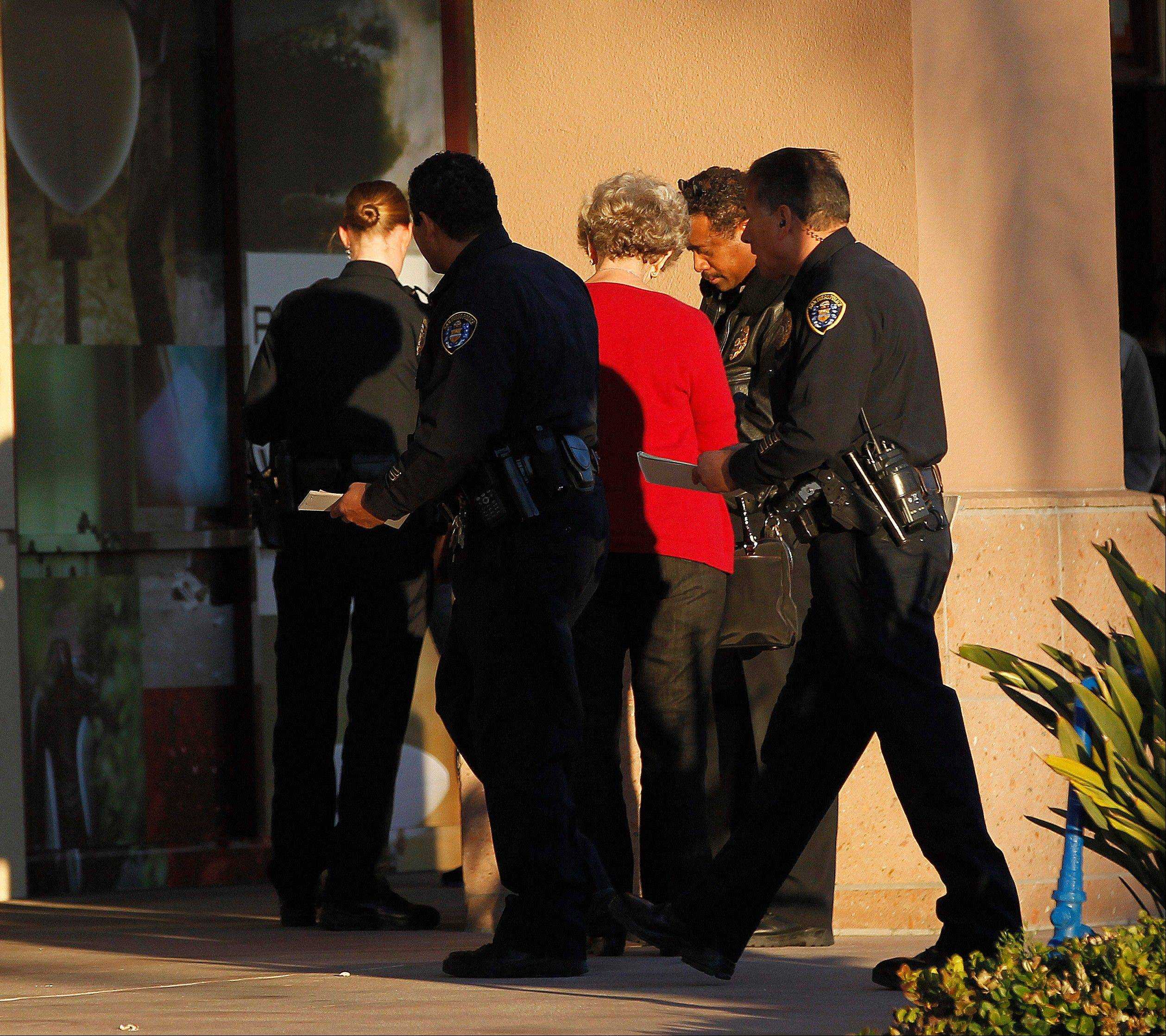 Police officers talk with a witness near a shooting at the Reading Cinemas in San Diego on Saturday evening.