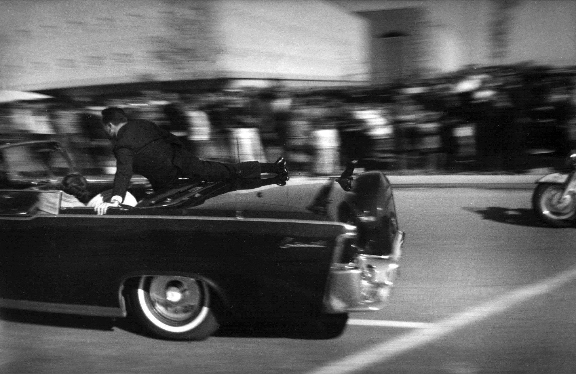 The limousine carrying mortally wounded President John F. Kennedy races toward the hospital seconds after he was shot in Dallas.
