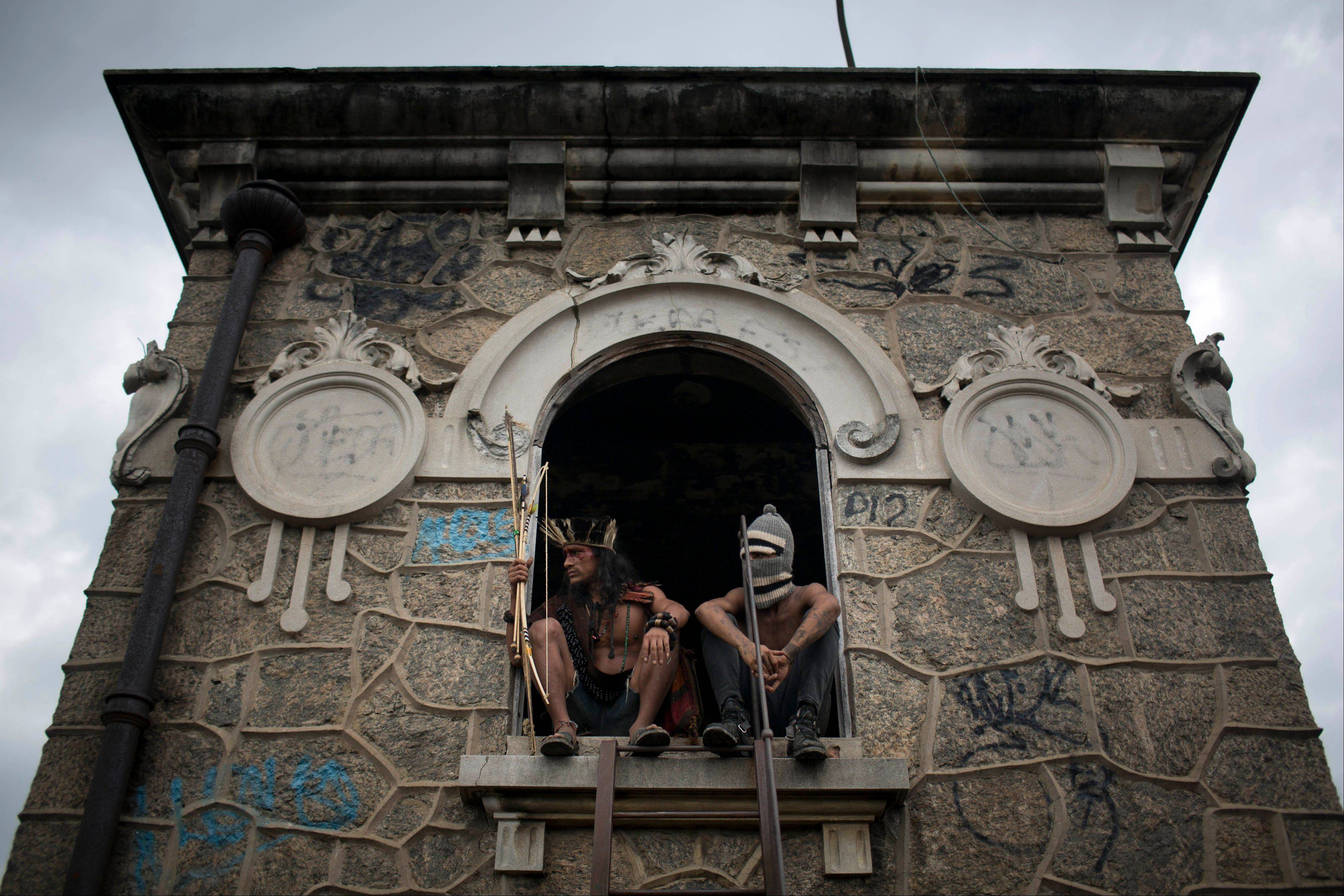 A man wearing a headdress and another wearing a ski mask sit Saturday on a windowsill on the site of an old Indian museum, in Rio de Janeiro, Brazil.