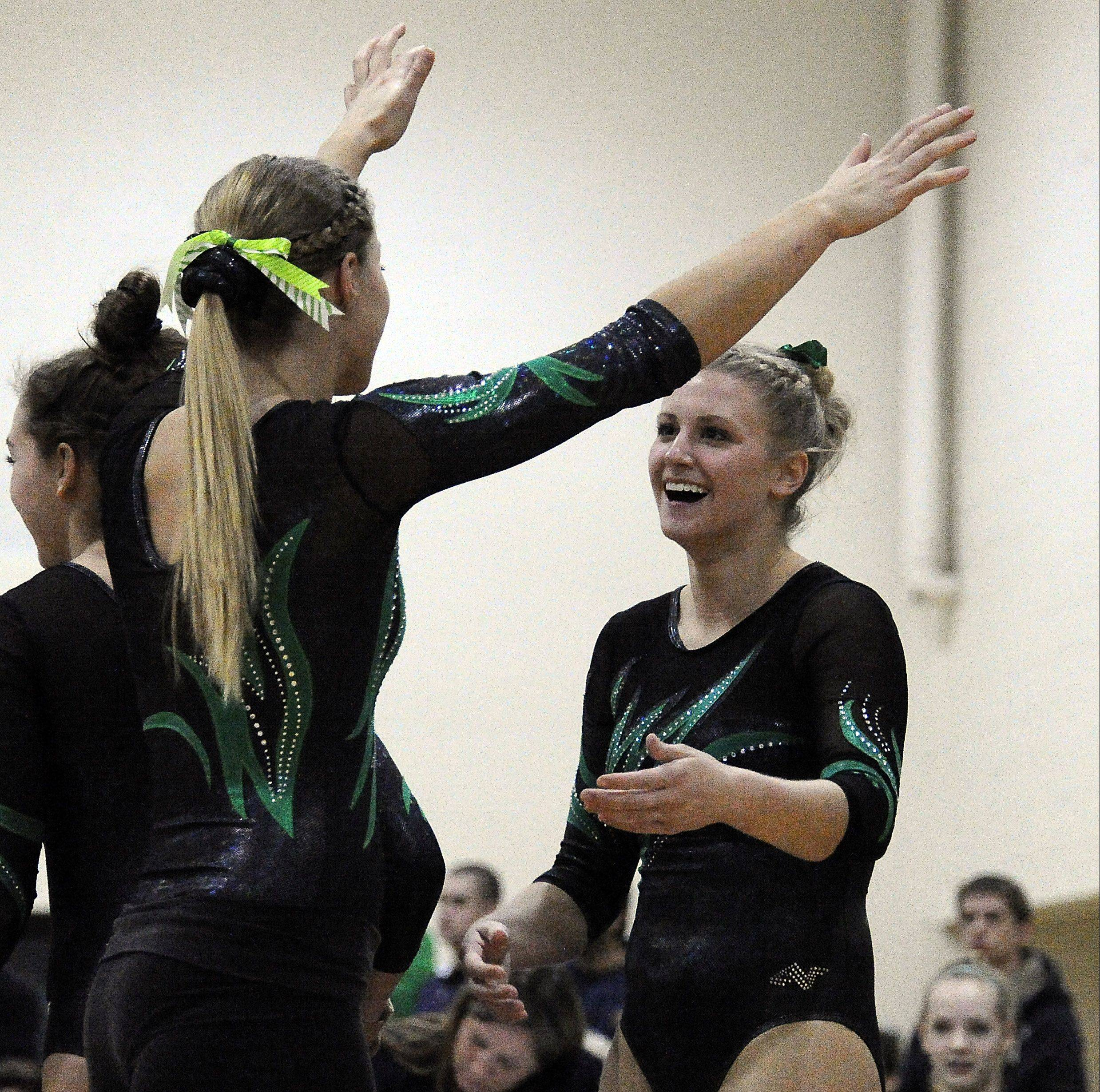 Fremd's Mary Smaga celebrates with her teammates after her vault routine at the Fremd Invitational on Saturday.