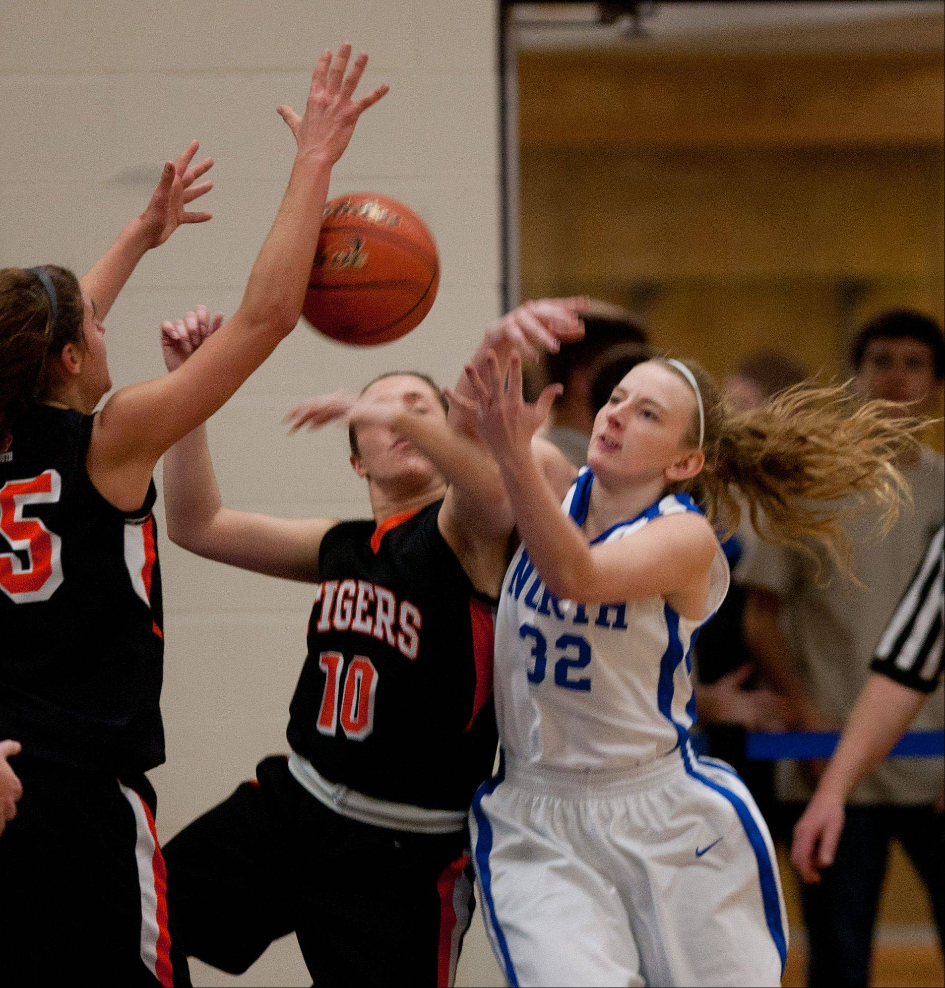 Wheaton Warrenville South�s Sierra Bisso (10), battles Wheaton North�s Abby Watts (32), during girls basketball action in Wheaton.