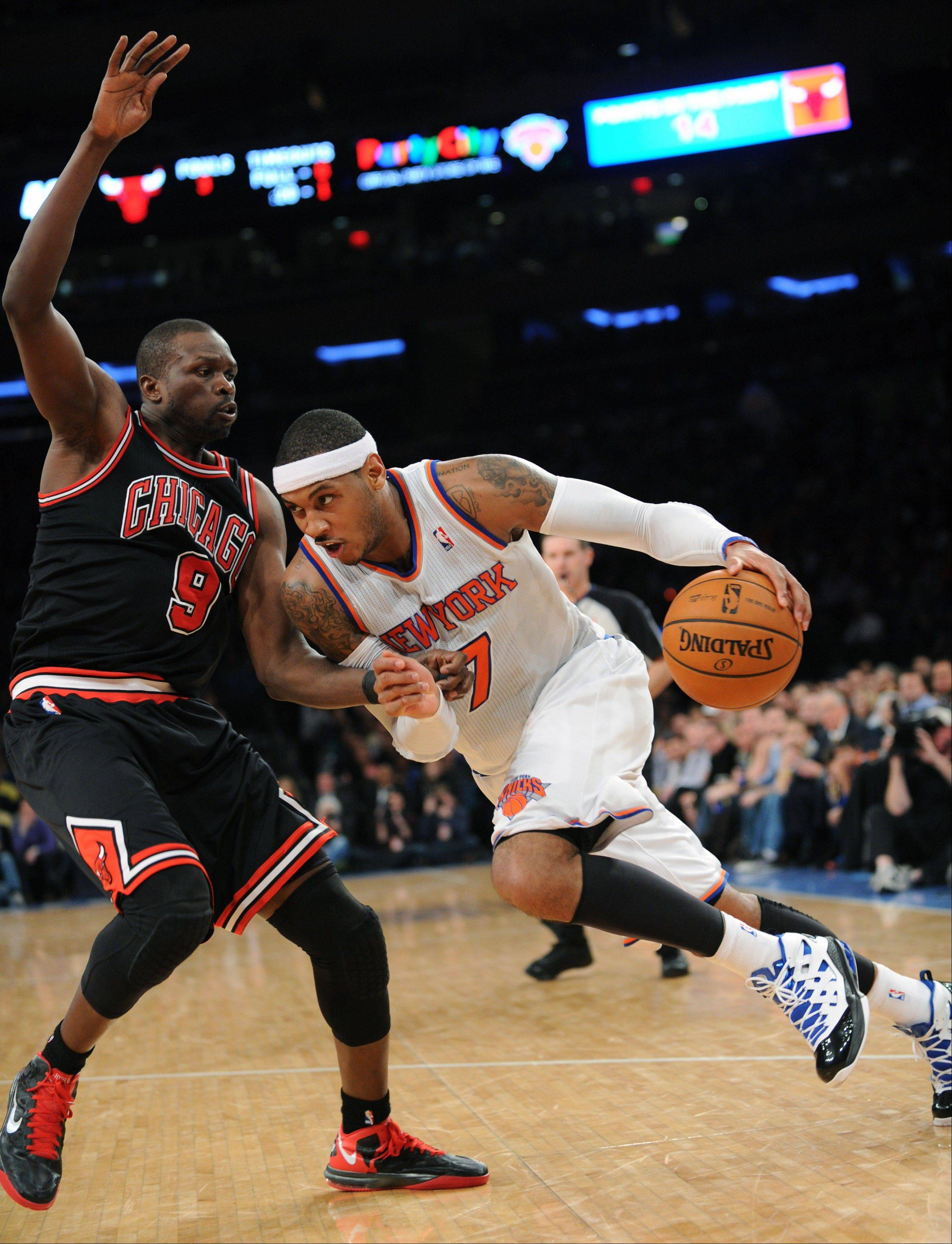 New York Knicks' Carmelo Anthony, right, attempts to drive to the basket as he is guarded by Chicago Bulls' Luol Deng, of Sudan, during the first half of an NBA basketball game Friday, Jan. 11, 2013, at Madison Square Garden in New York. (AP Photo/Bill Kostroun)