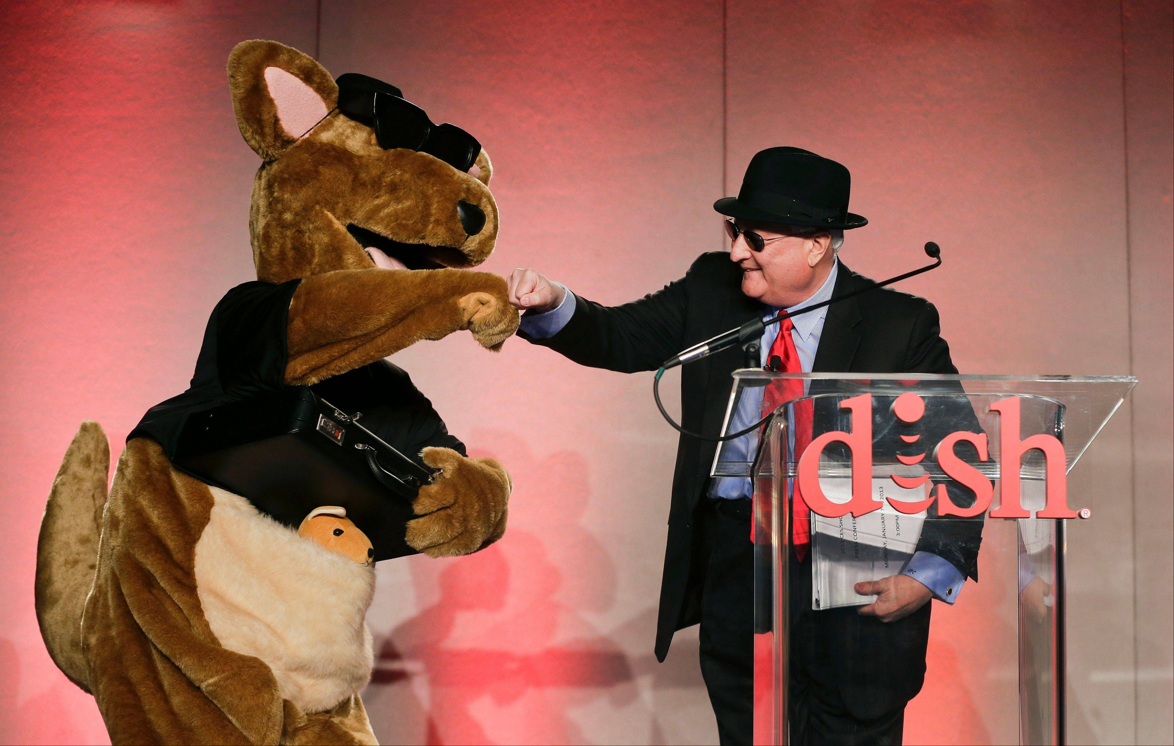 DISH Network president and CEO Joe Clayton greets the company mascot, Hopper, at the start of a news conference during press day at the Consumer Electronics Show.