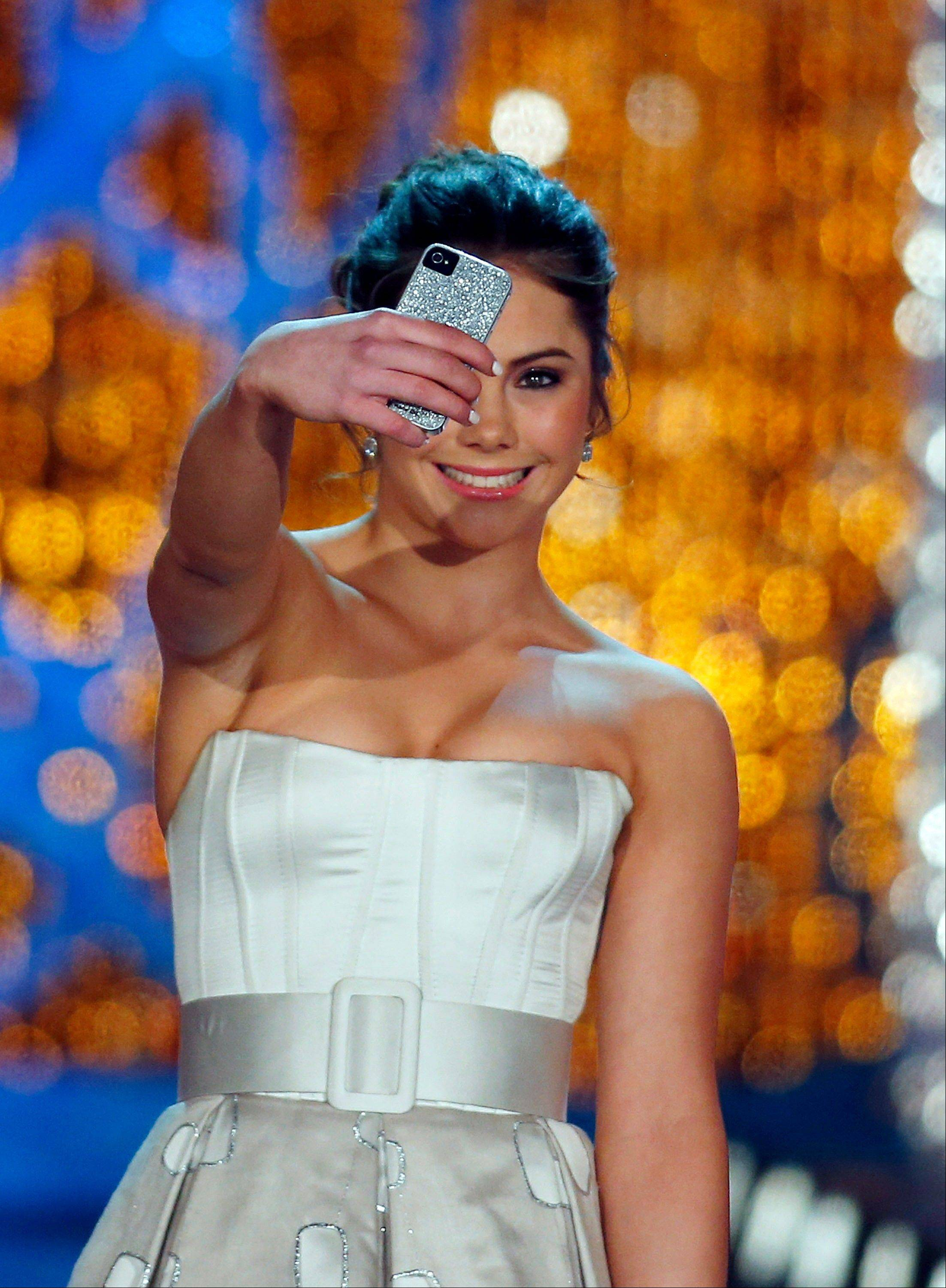 Miss America judge McKayla Maroney photographs herself onstage before the pageant on Saturday, Jan. 12, 2013, in Las Vegas.
