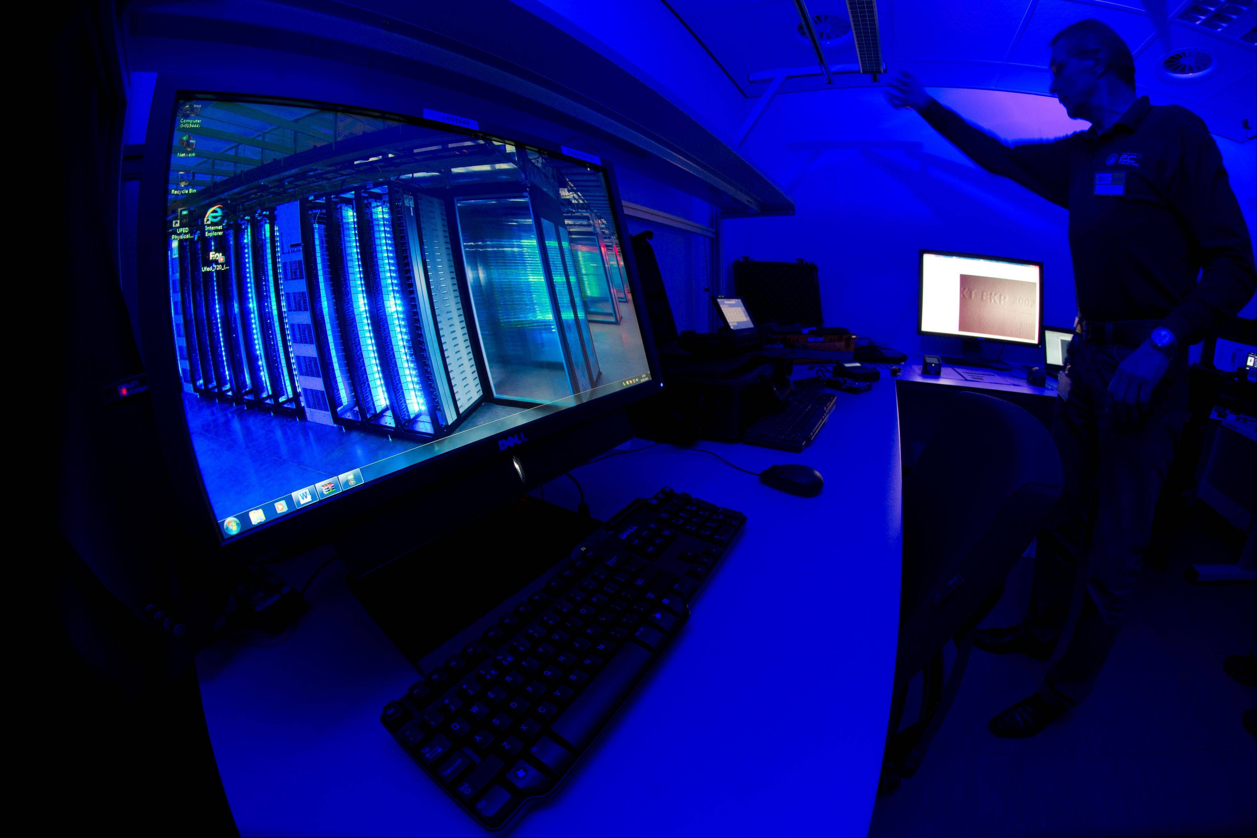 A member of the Cybercrime Center turns on the light in a lab Friday during a media tour at the occasion of the official opening of the Cybercrime Center at Europol headquarters in The Hague, Netherlands. The lab is housed in a cage of Faraday and is used amongst others to analyze computer hard disks, mobile phones and smart phones.