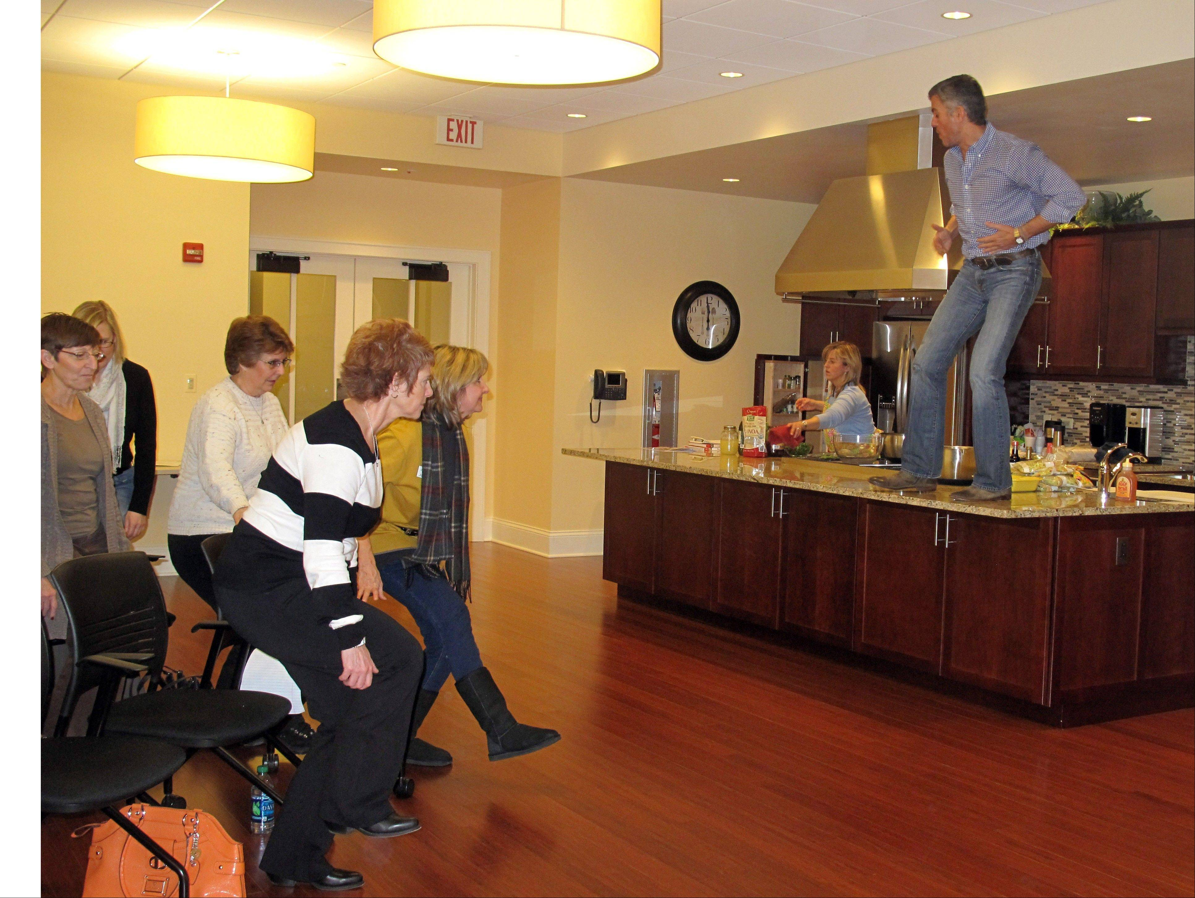 Celebrity trainer and author Jim Karas leads a crowd in squats from atop a kitchen counter at the LivingWell Cancer Resource Center in Geneva, where he spoke Saturday about ways cancer patients and others can boost immunity.