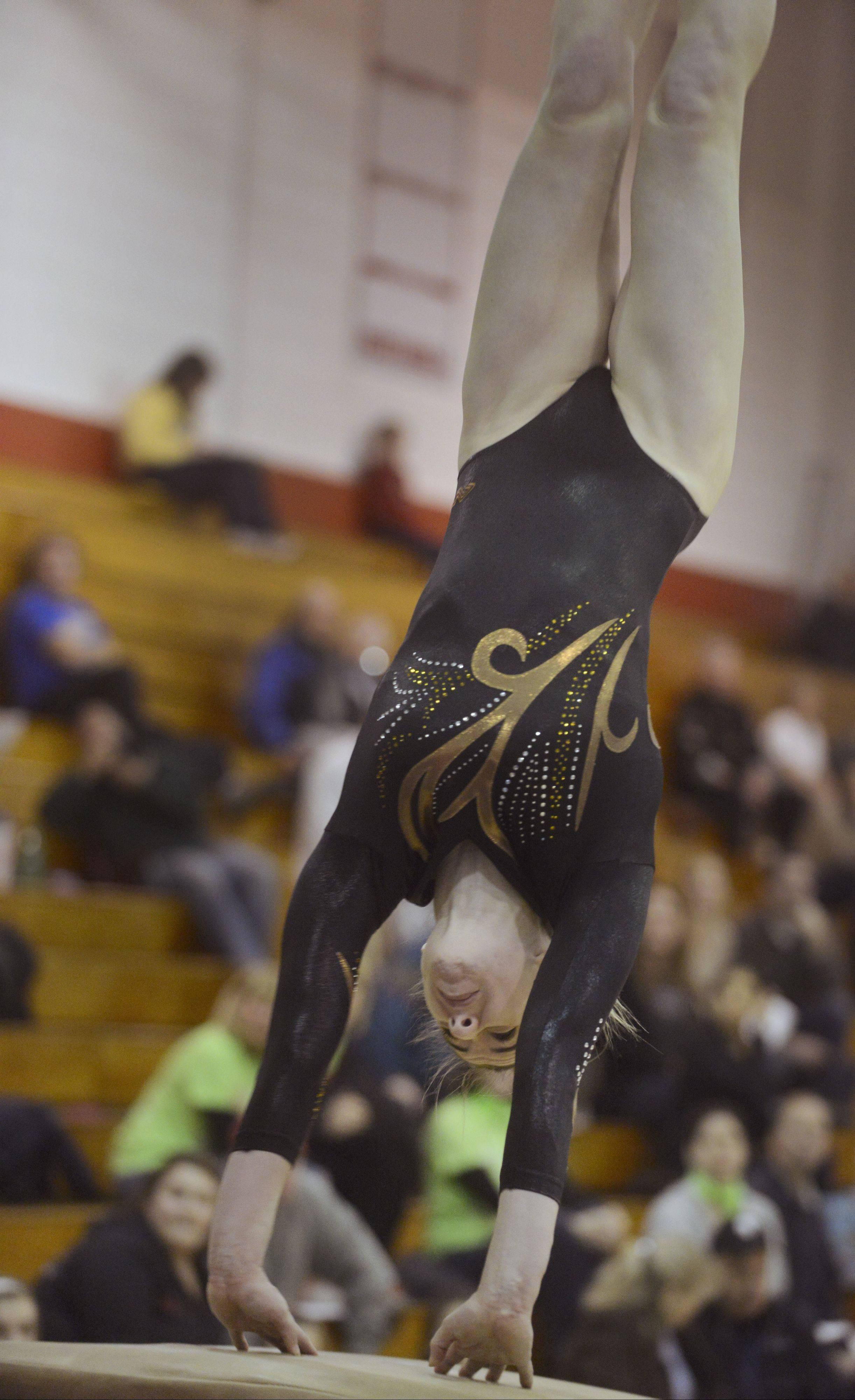 Carmel's Lauren Feely competes on vault during the Lake County girls gymnastics meet at Mundelein on Saturday. She hit a 9.95 on the event.