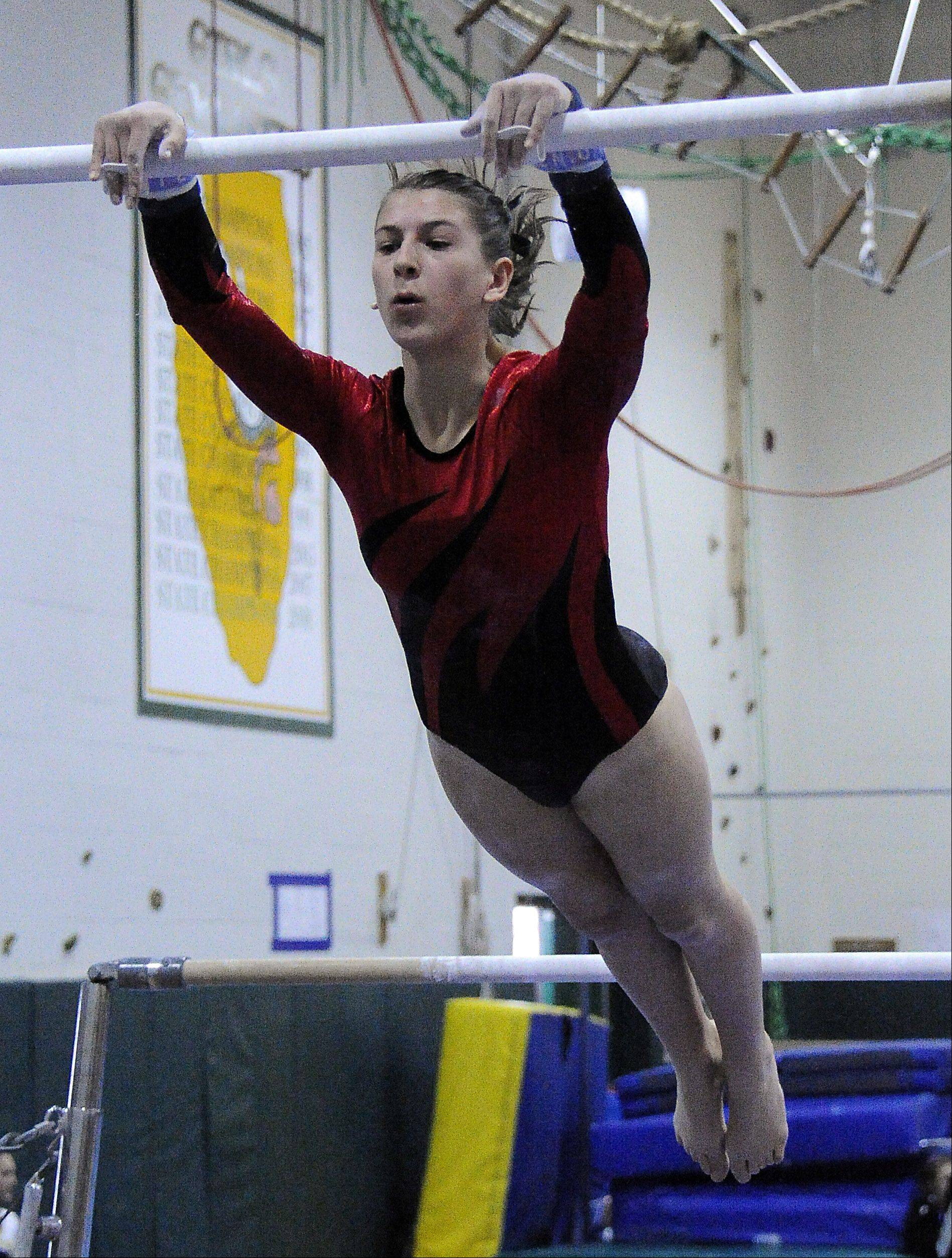 Naperville Central's Lea Savard on the bars at the Fremd Invitational on Saturday.