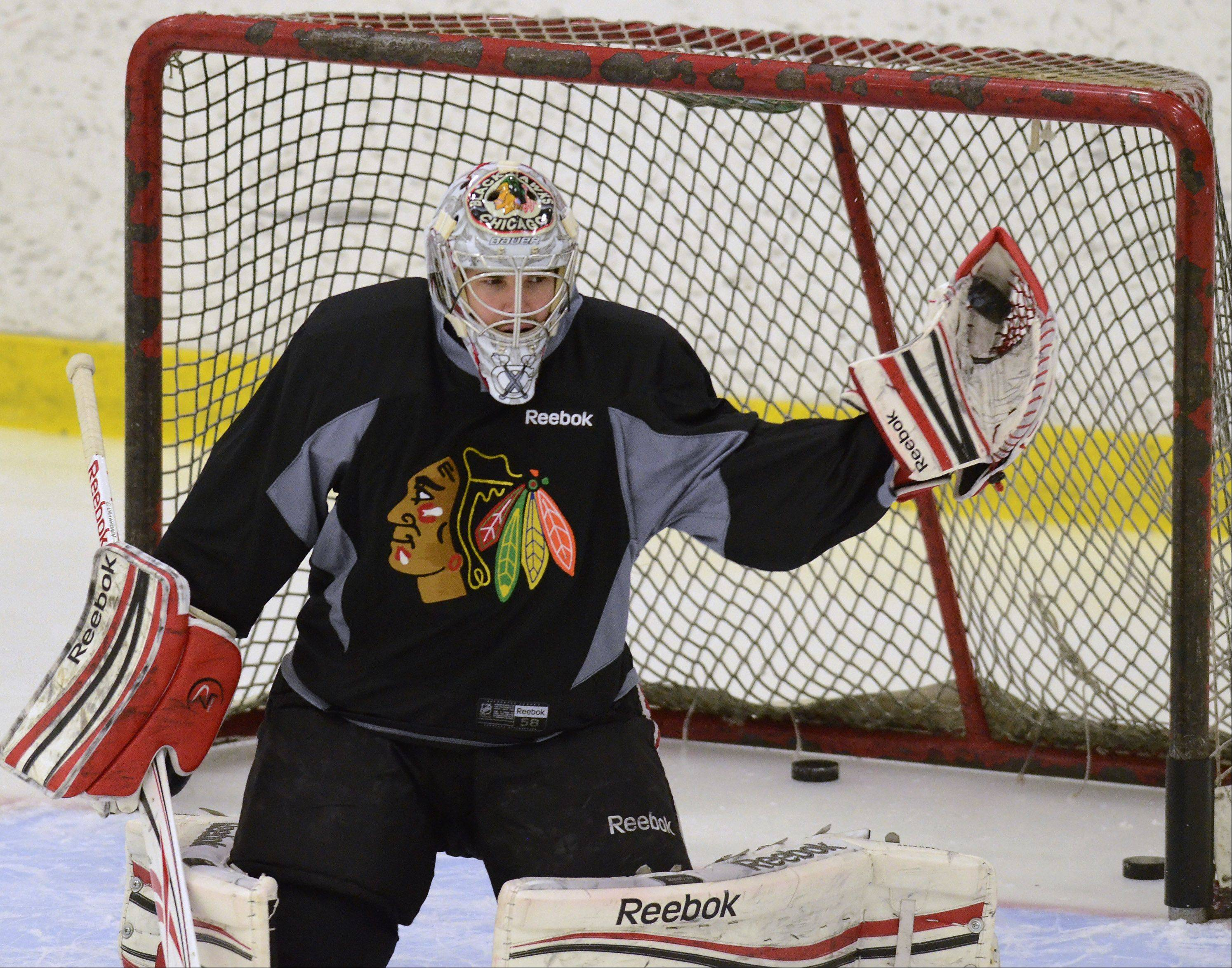 Nobody will be under more pressure this lockout-shortened Blackhawks season than goalie Corey Crawford makes a glove save as Blackhawks players hold an informal practice at Johnny's Ice House.