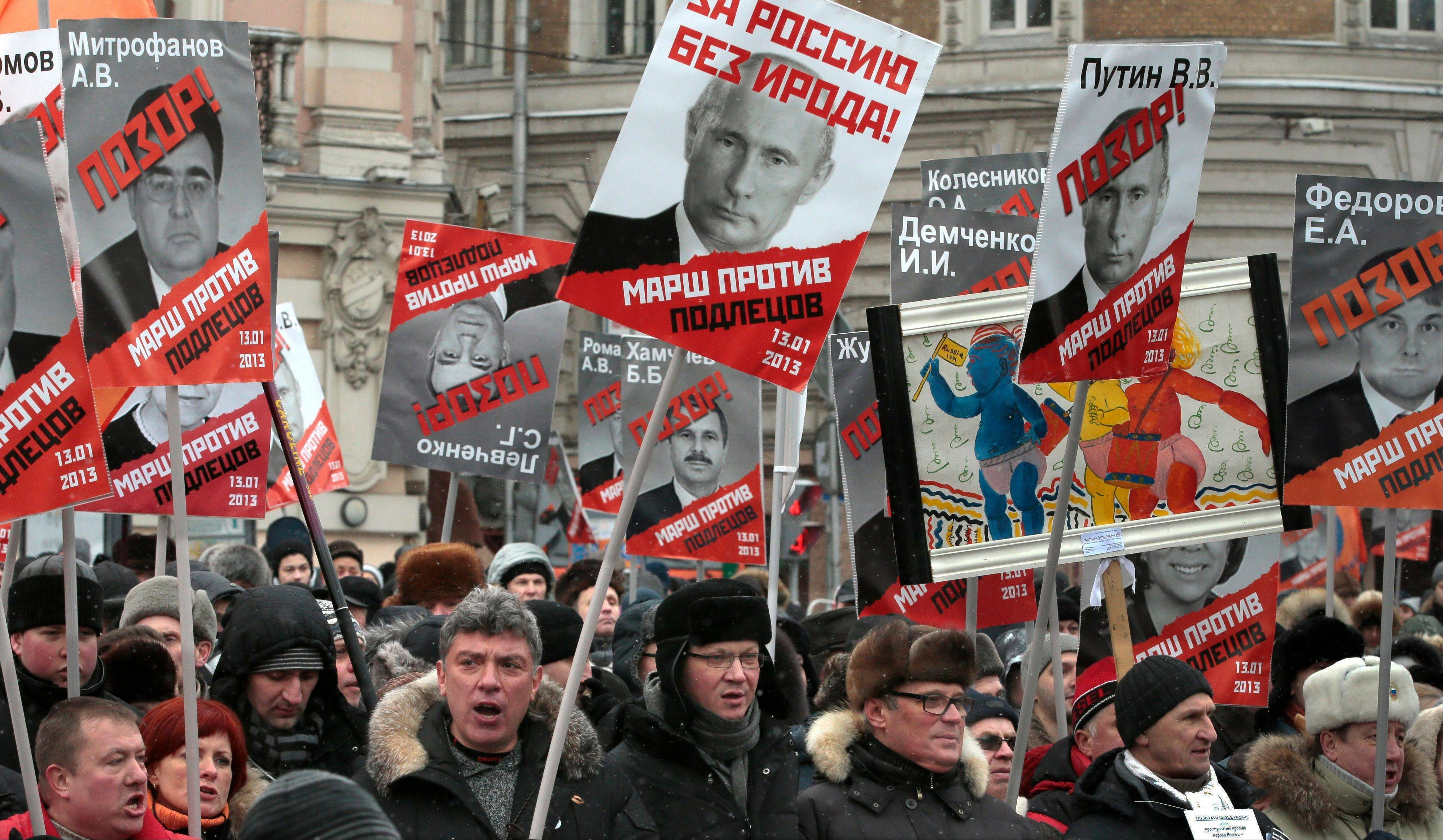 People carry posters of Russian President Vladimir Putin with the words reading �For Russia without Herod!� during a protest rally in Moscow Sunday. The reference to Herod refers to the biblical ruler who murdered members of his own family and initiated the killing of infants in Bethlehem during the time of Jesus.