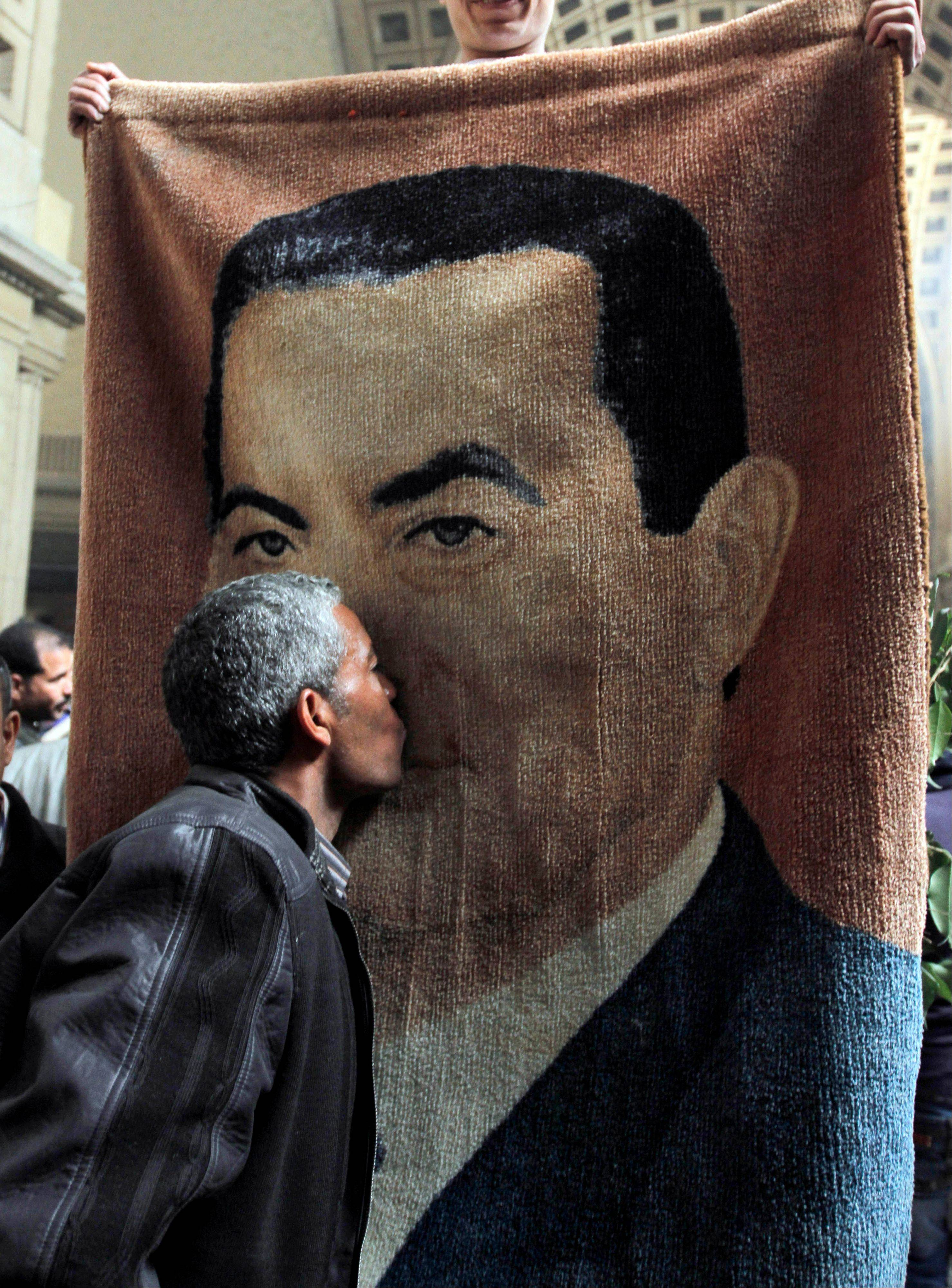 An Egyptian kisses an image of ousted former Egyptian President Hosni Mubarak, woven on a carpet that was brought in by Mubarak supporters, as they celebrate an appeal granted by a court, in Cairo on Sunday.