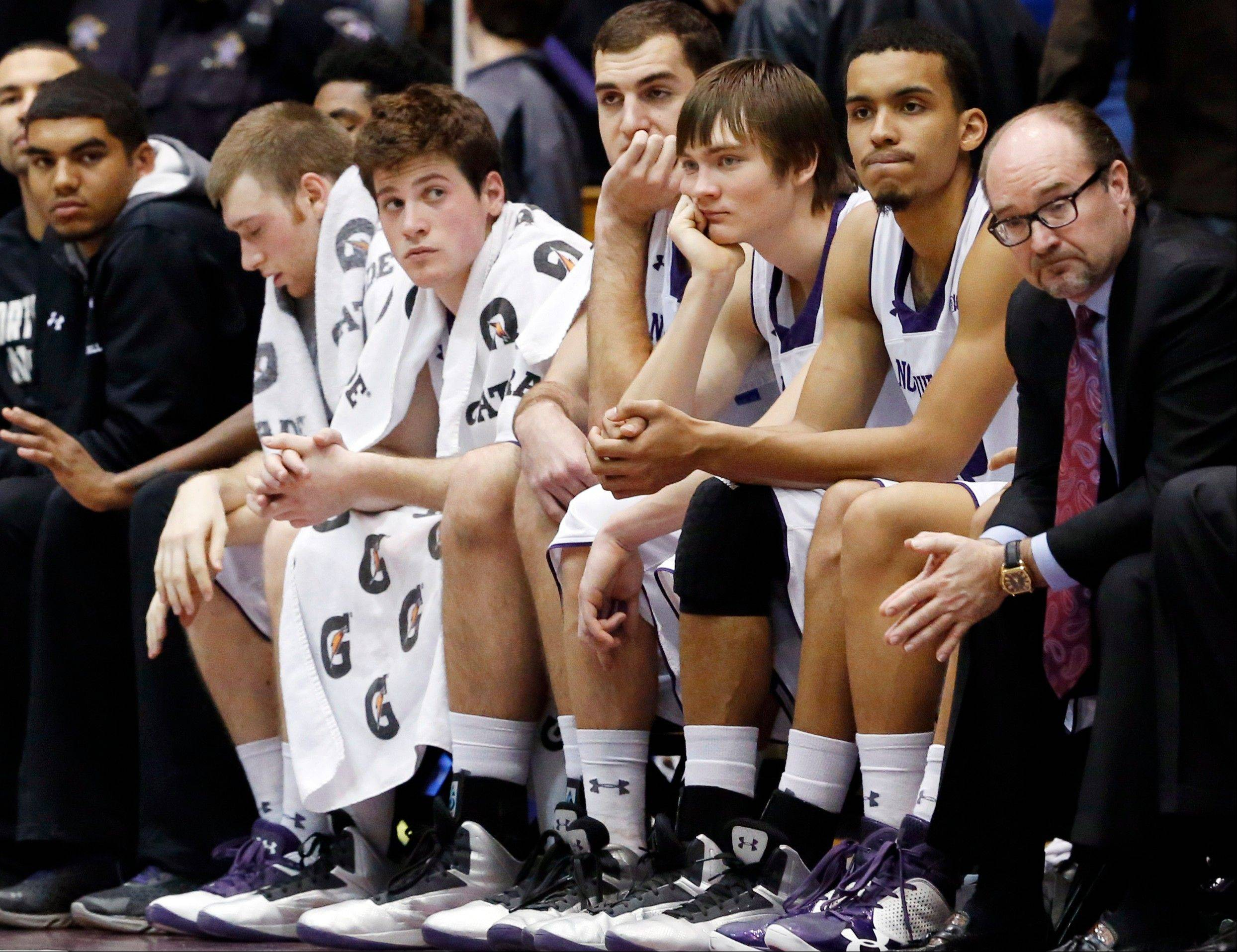 Northwestern players react as they watch teammates play during the second half of an NCAA college basketball game against Iowa in Evanston, Ill., on Sunday, Jan. 13, 2013. Iowa won 70-50.