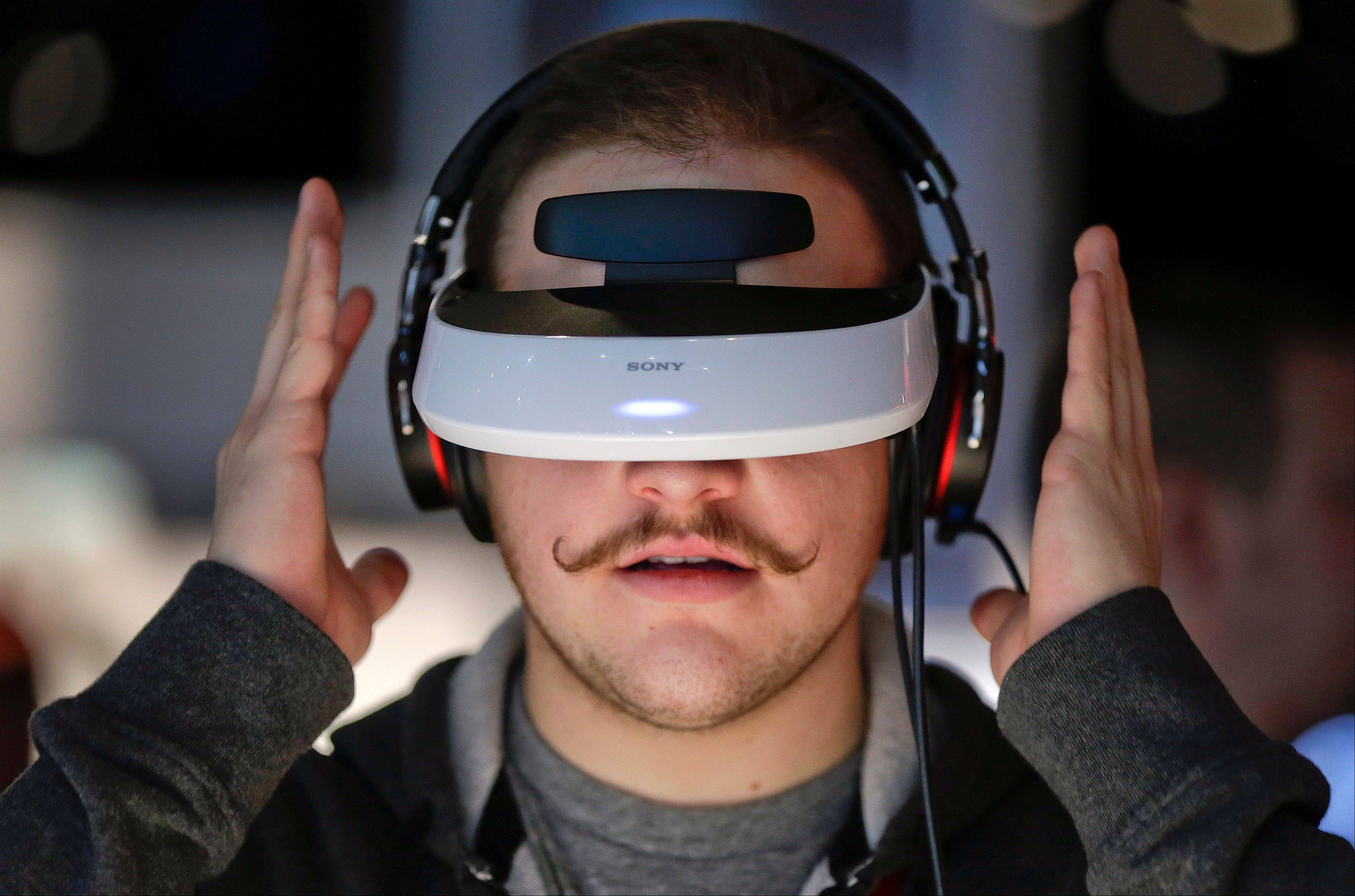 Justin Bredeau, of Las Vegas, tries out a Sony 3-D personal viewer at the Consumer Electronics Show, Friday in Las Vegas. The viewer simulates watching a 150-inch screen from 12 feet away.