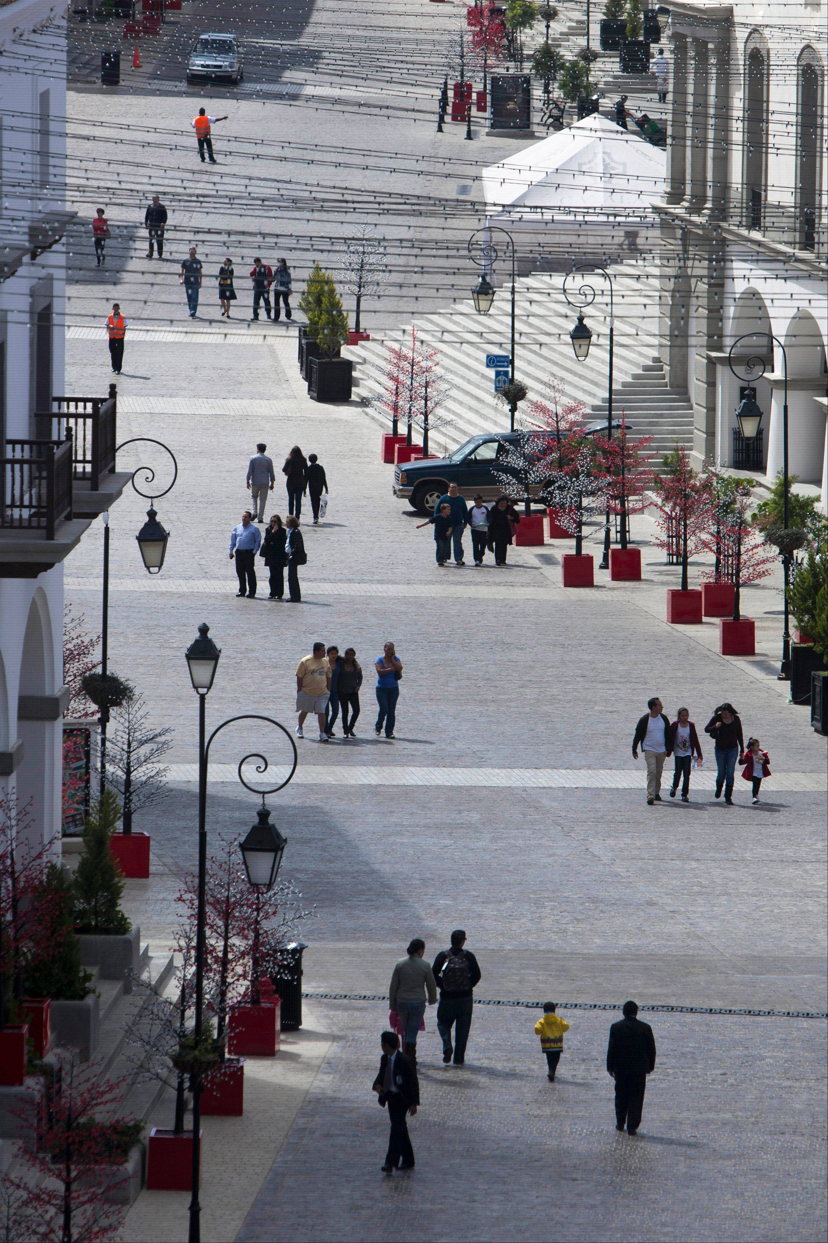 People walk in Paseo Cayala, a nearly independent city on the edges of Guatemala City. Some urbanists and architects are skeptical the project can thrive over the long term in a country with one of the world's highest homicide rates and with roughly half of its 14 million people in poverty.