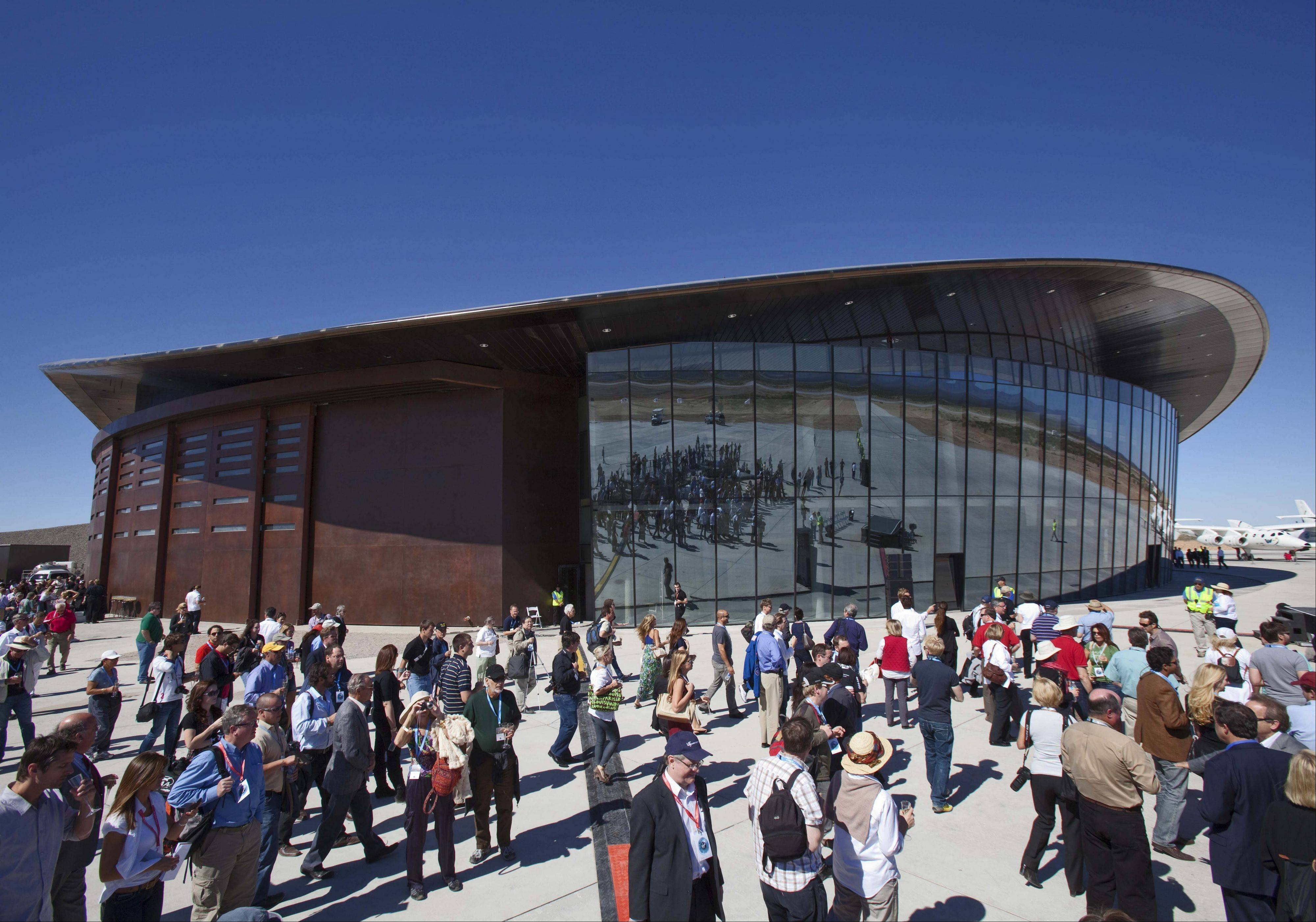 Guests stand outside the new Spaceport America hangar in Upham, N.M. Spaceport America officials are urging legislators to limit potential lawsuits from wealthy outer space tourists who take off from New Mexico, saying such a bill is crucial to the future of the project.