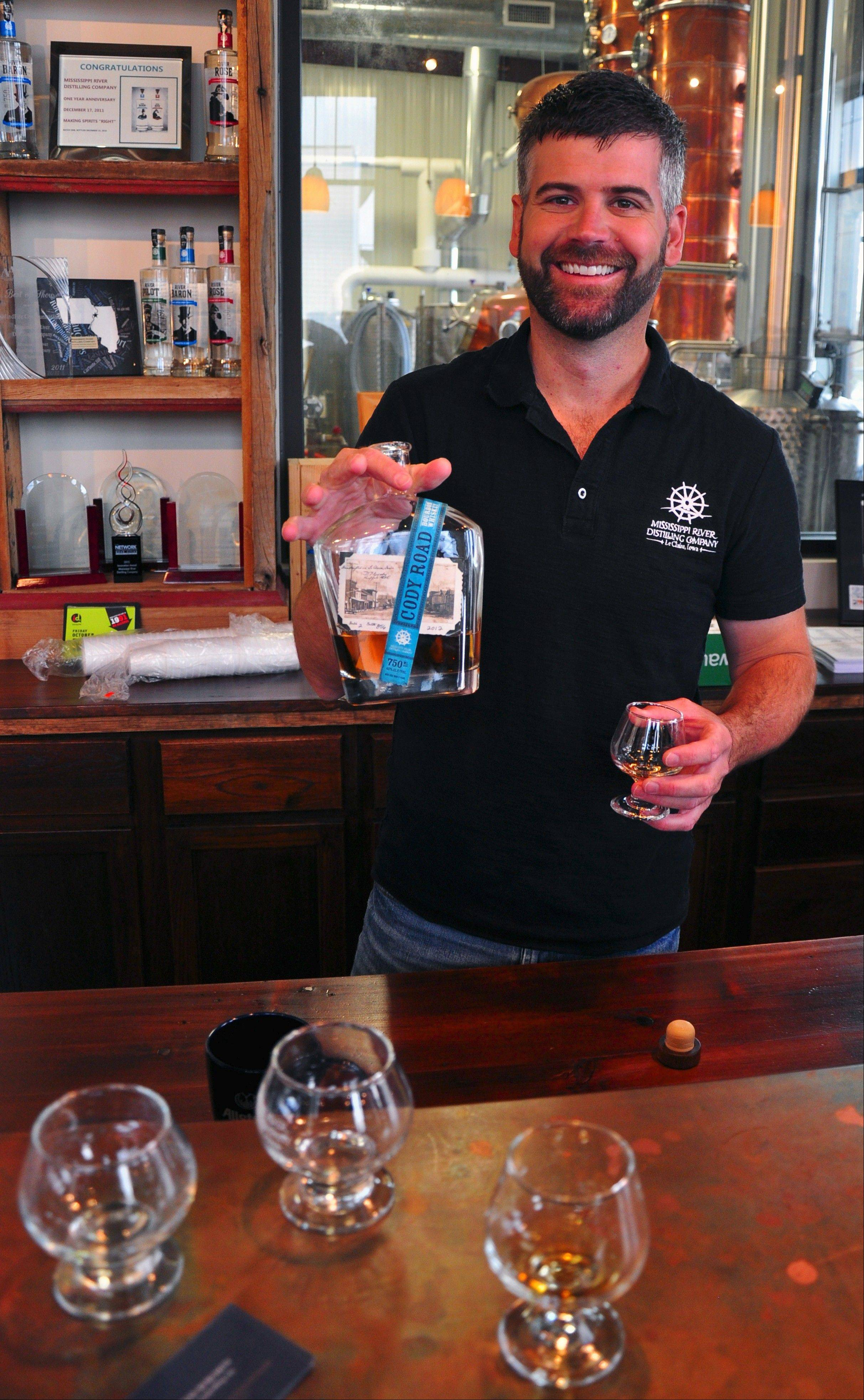 Sean McQueen pours visitors a sample of the first batch of bourbon distilled last fall at Mississippi River Distilling Co.