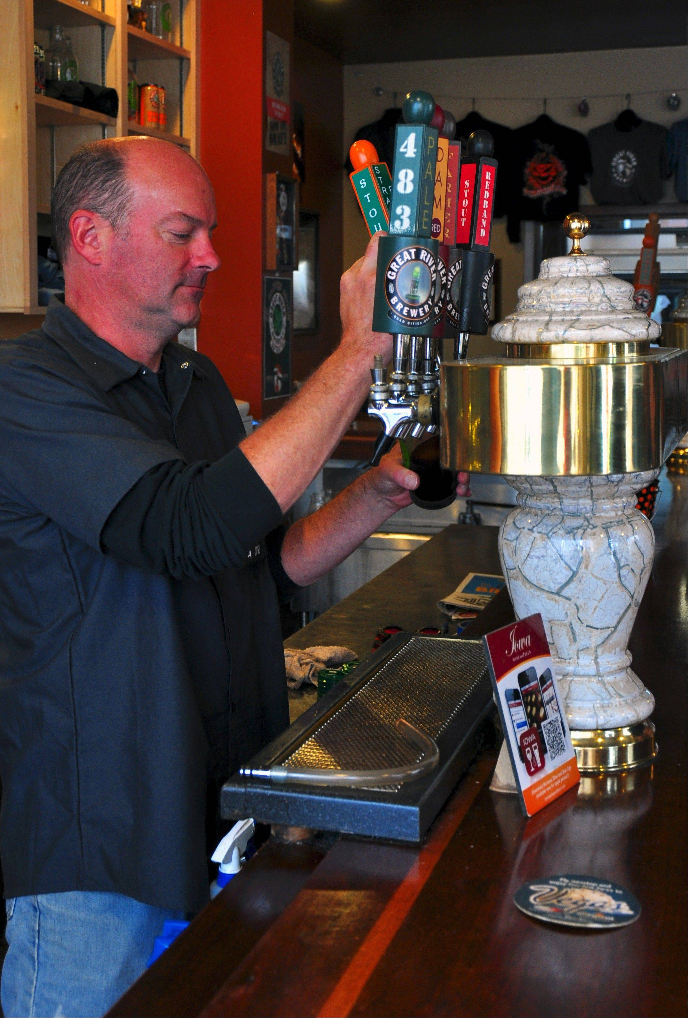 Dann Cornelis mans the taps in the Brewer's Lounge at Great River Brewery in Davenport, Iowa.