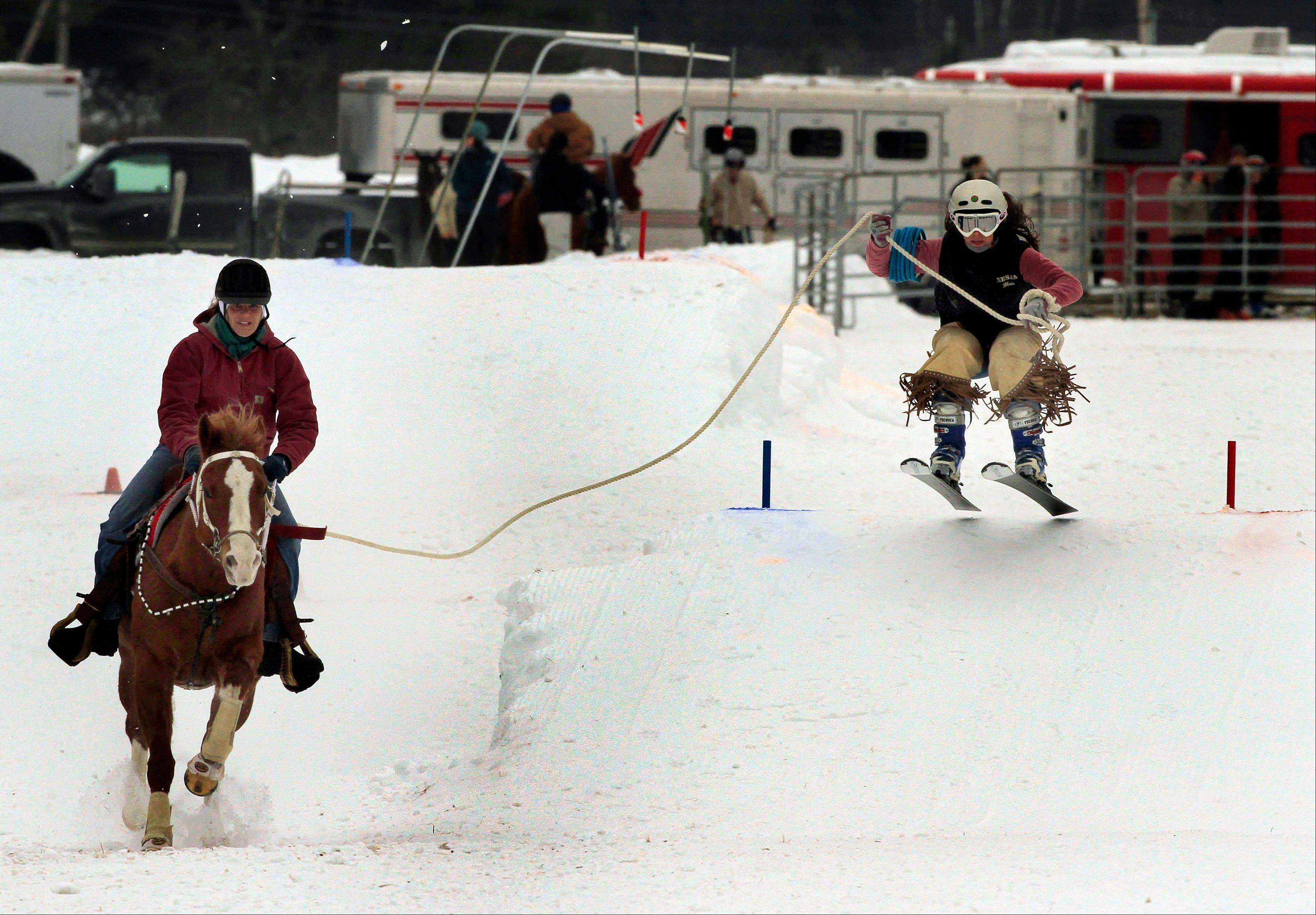 Skier Blair Weathers of Wilmot, N.H., flies off a jump as he is pulled by Summertime and rider Jennifer Elliot during the Skijoring competition at the Newport Winter Carnival in Newport, N.H. Skijoring is a sport in which a skier is pulled over snow or ice, generally by a horse.
