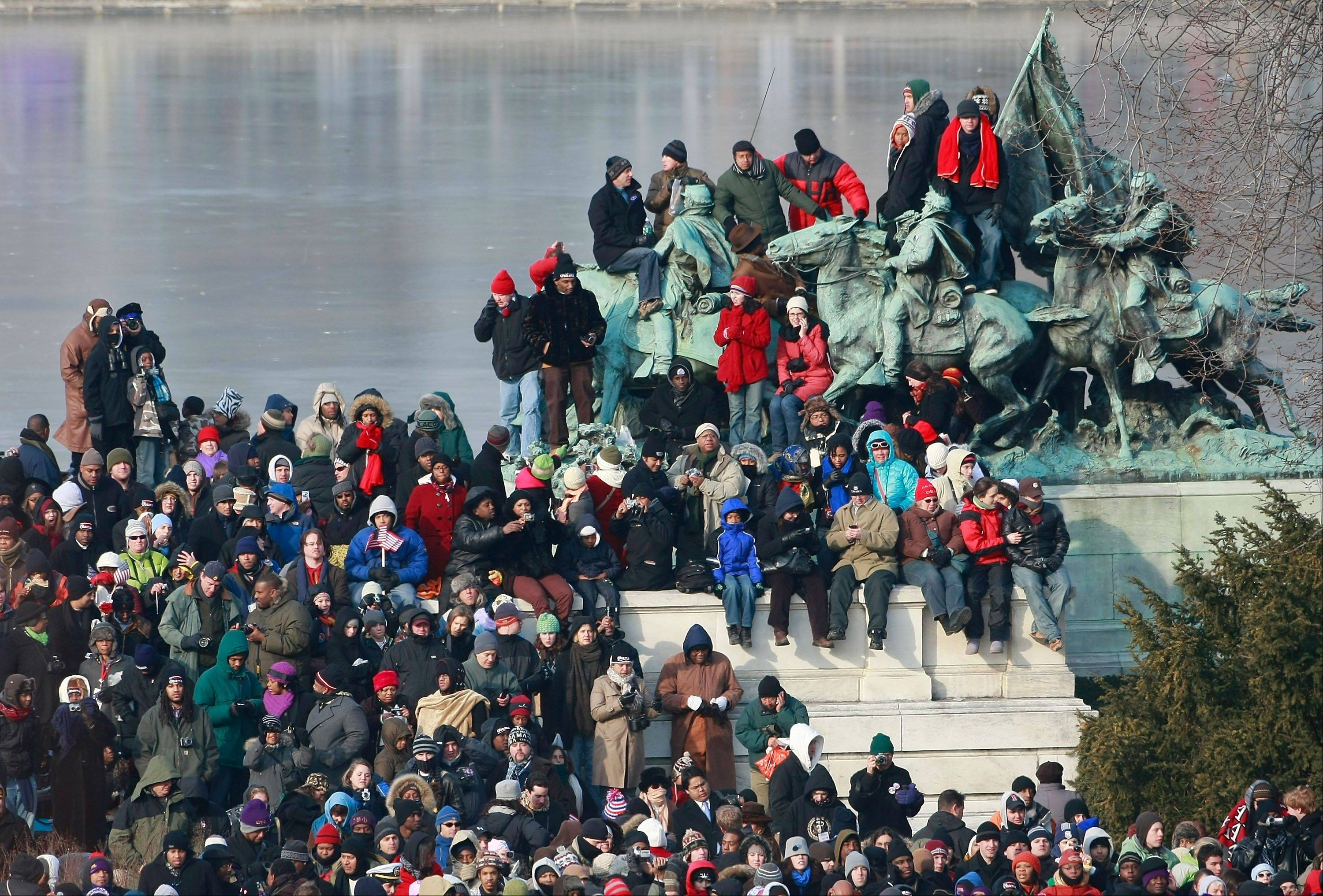 This Jan. 20, 2009 pool-file photo shows crowds standing on and near a statue next to the on the National Mall ahead of the inauguration of Barack Obama as the 44th President of the United States of America.